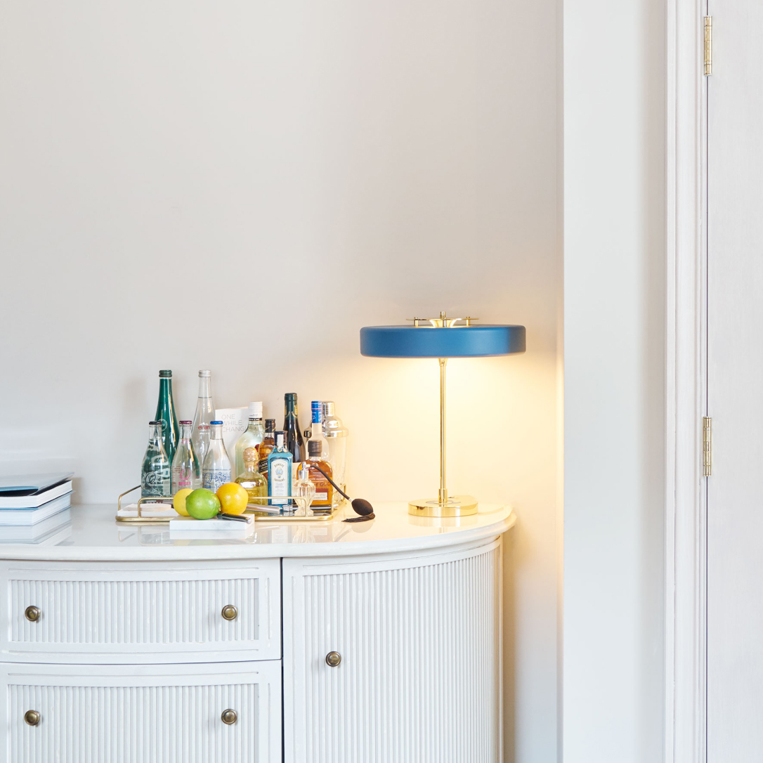 A white dresser with a lamp and cocktail making paraphenalia on it.