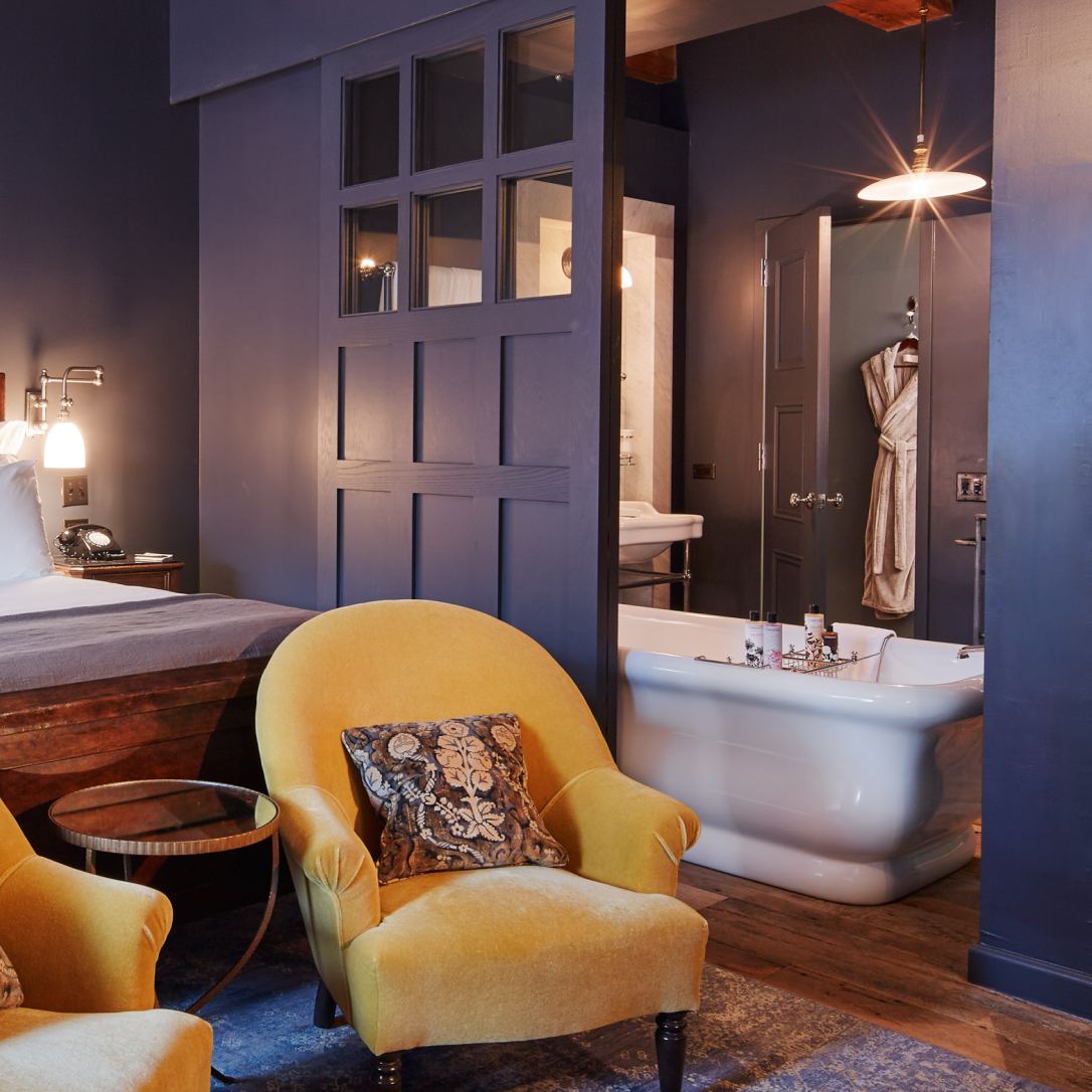 A bedroom with a yellow armchair and a roll top bath in the background.