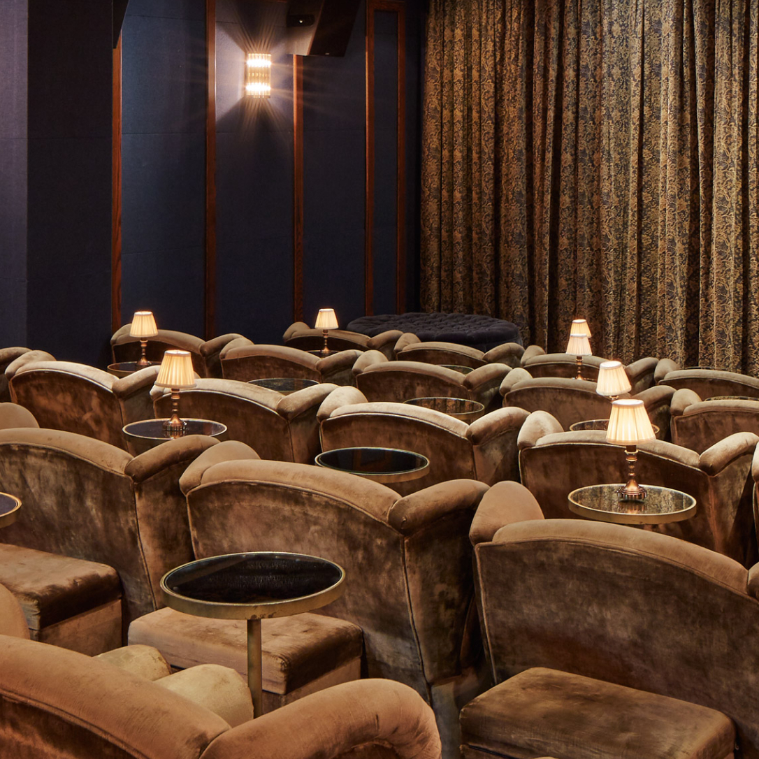 Rows of cinema seats and a curtain over a screen.