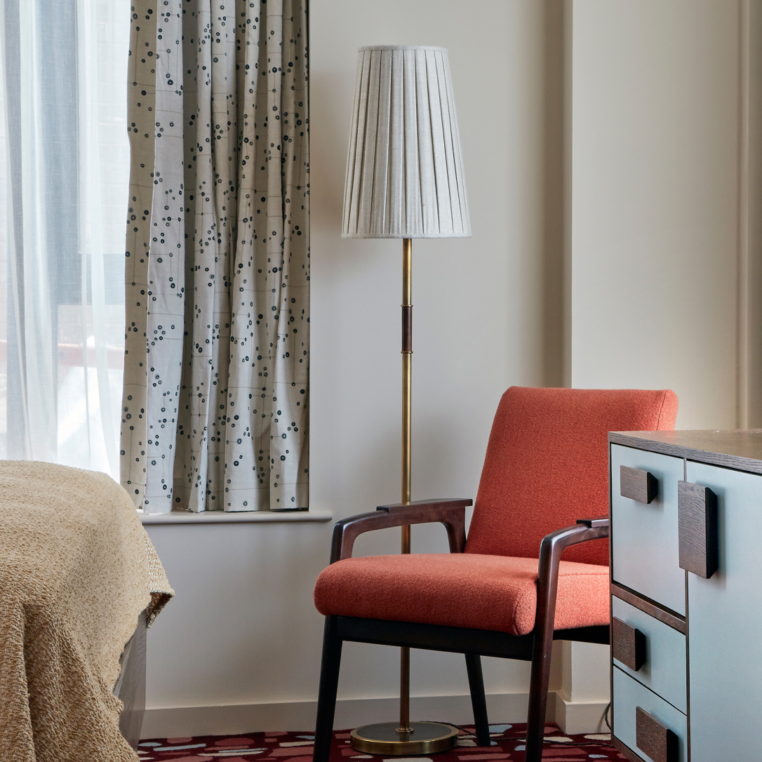 The corner of a bedroom with a chair and a floor lamp.