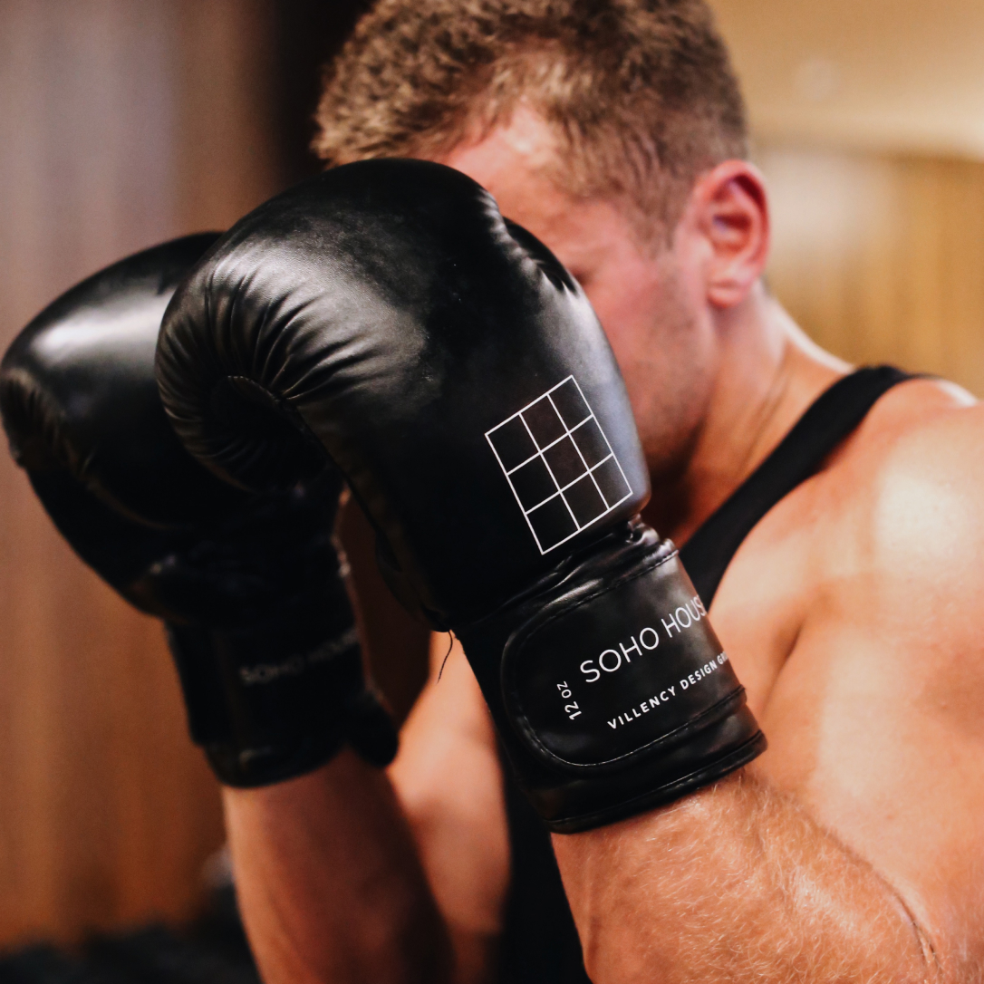 A man shields his face with boxing gloves.