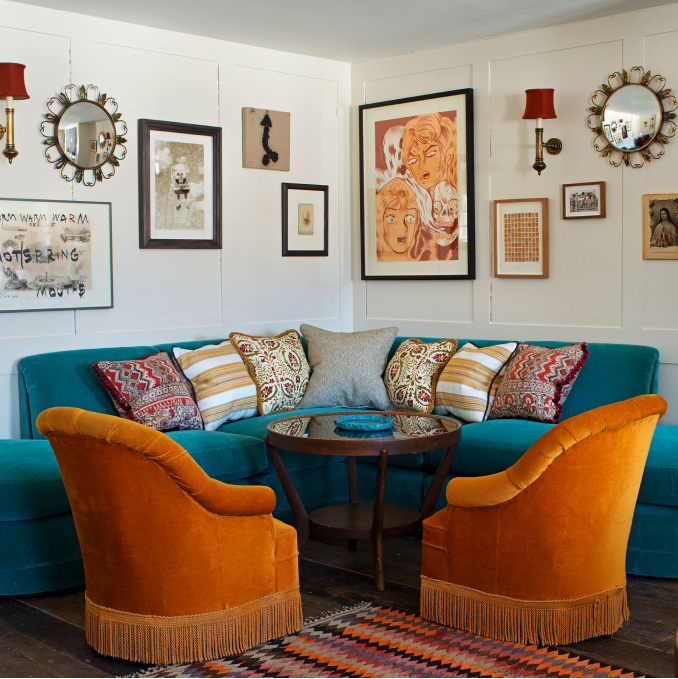 A blue corner sofa and two orange chairs.