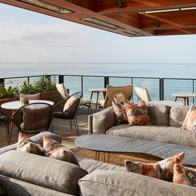 An outdoor terrace with sofas and tables overlooking the sea.