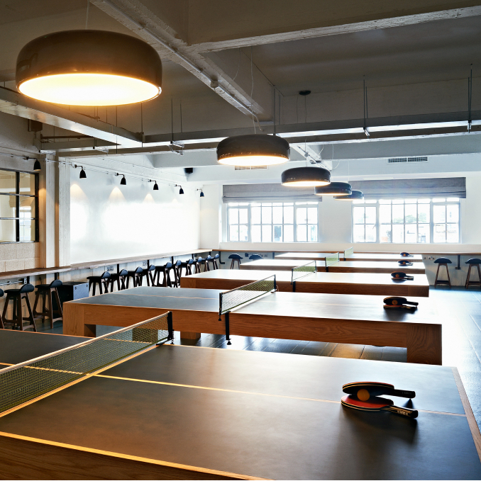 A room containing a row of table tennis tables.