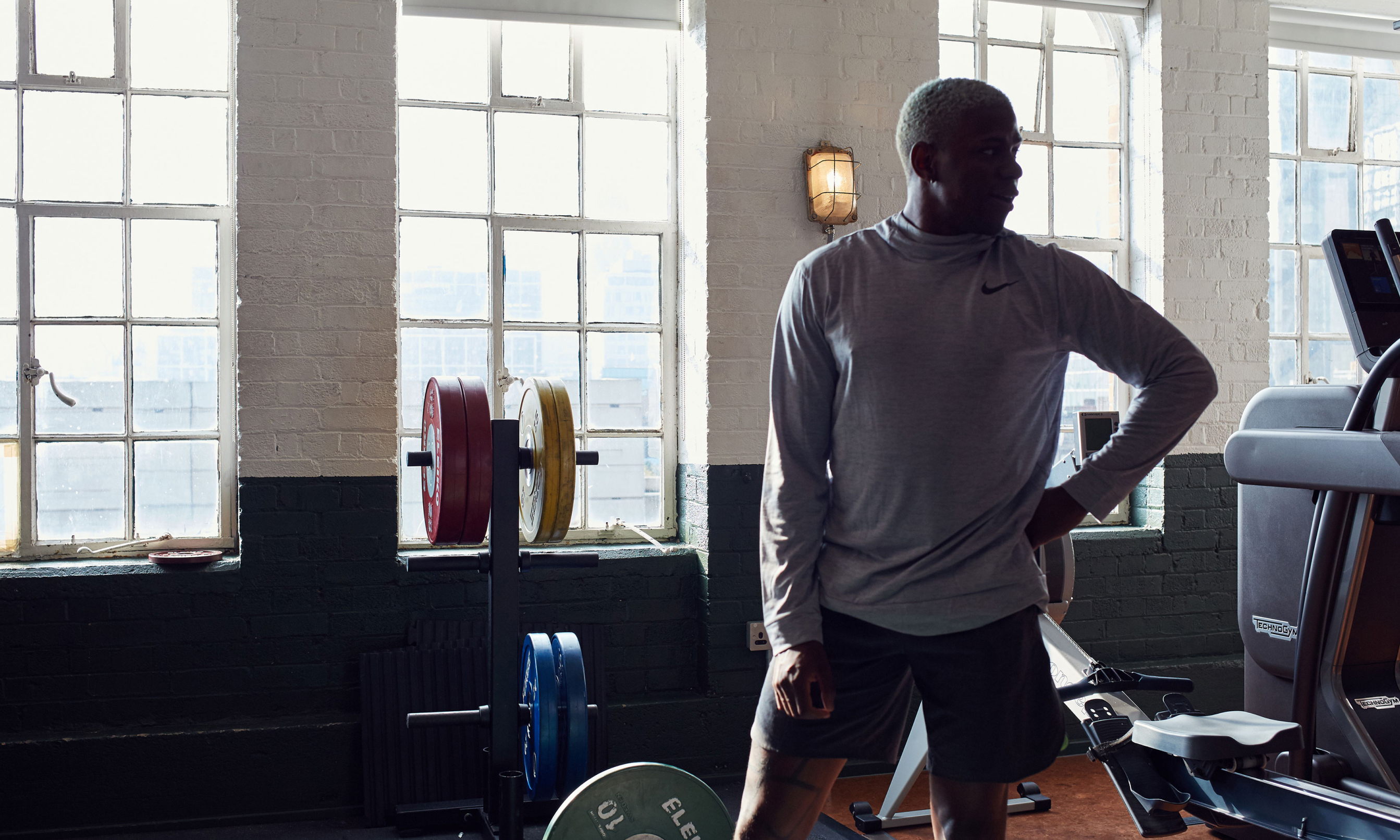 A man standing in a gym surrounded by weights.