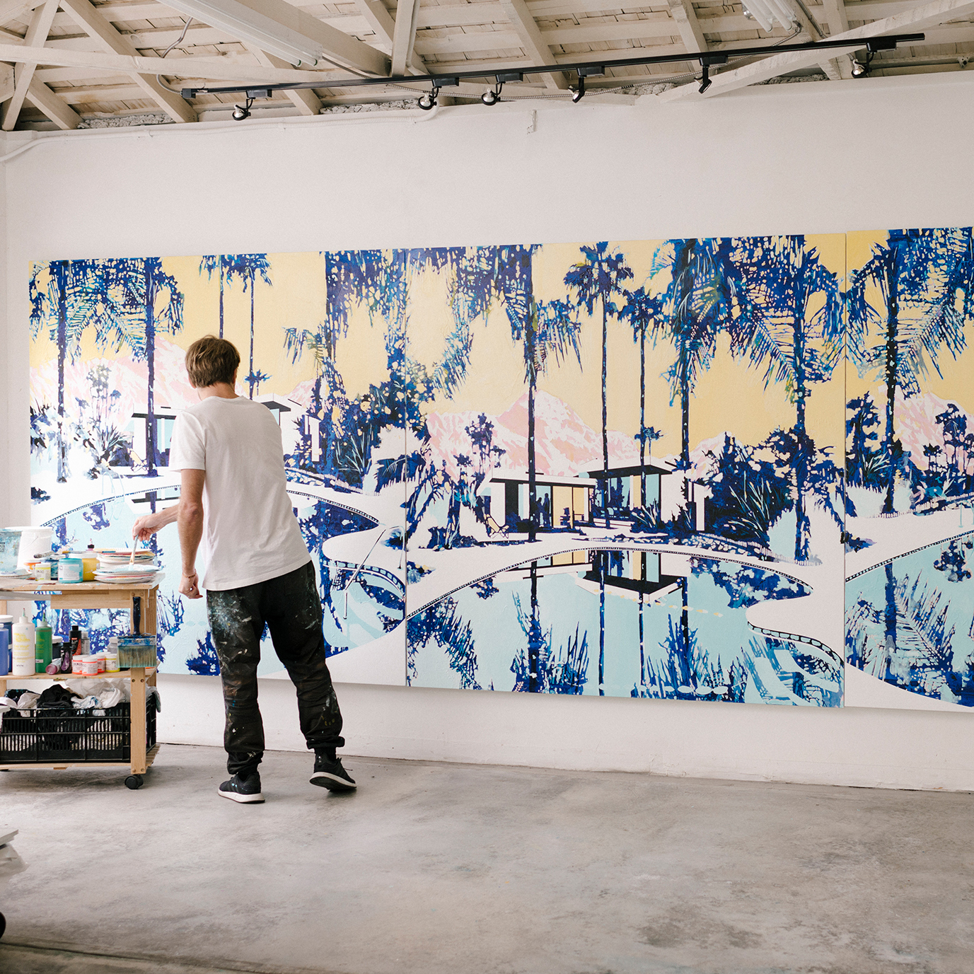man painting a large mural in a studio