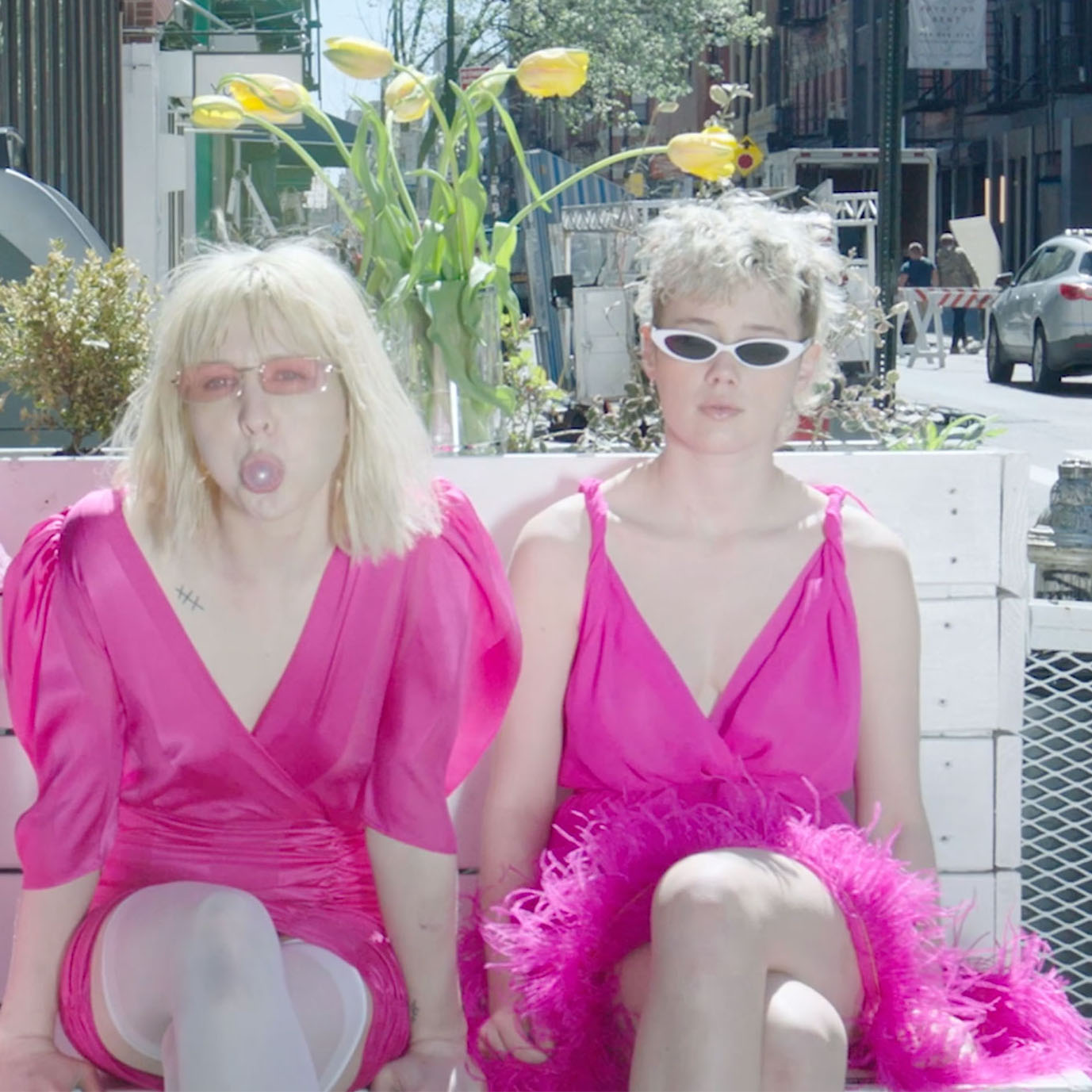 three women on a bench in city in pink dresses
