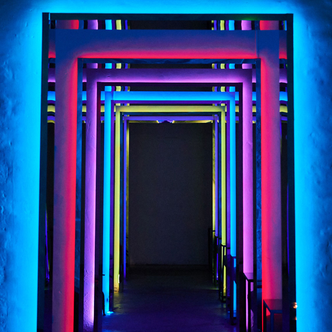 a tunnel lit with multiple neon colours
