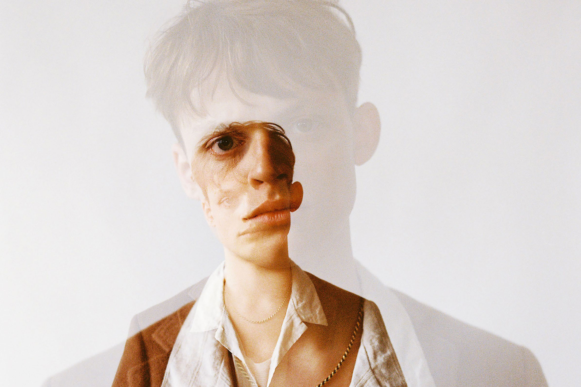 A double exposure of a young man wearing a seventies style shirt and jacket.