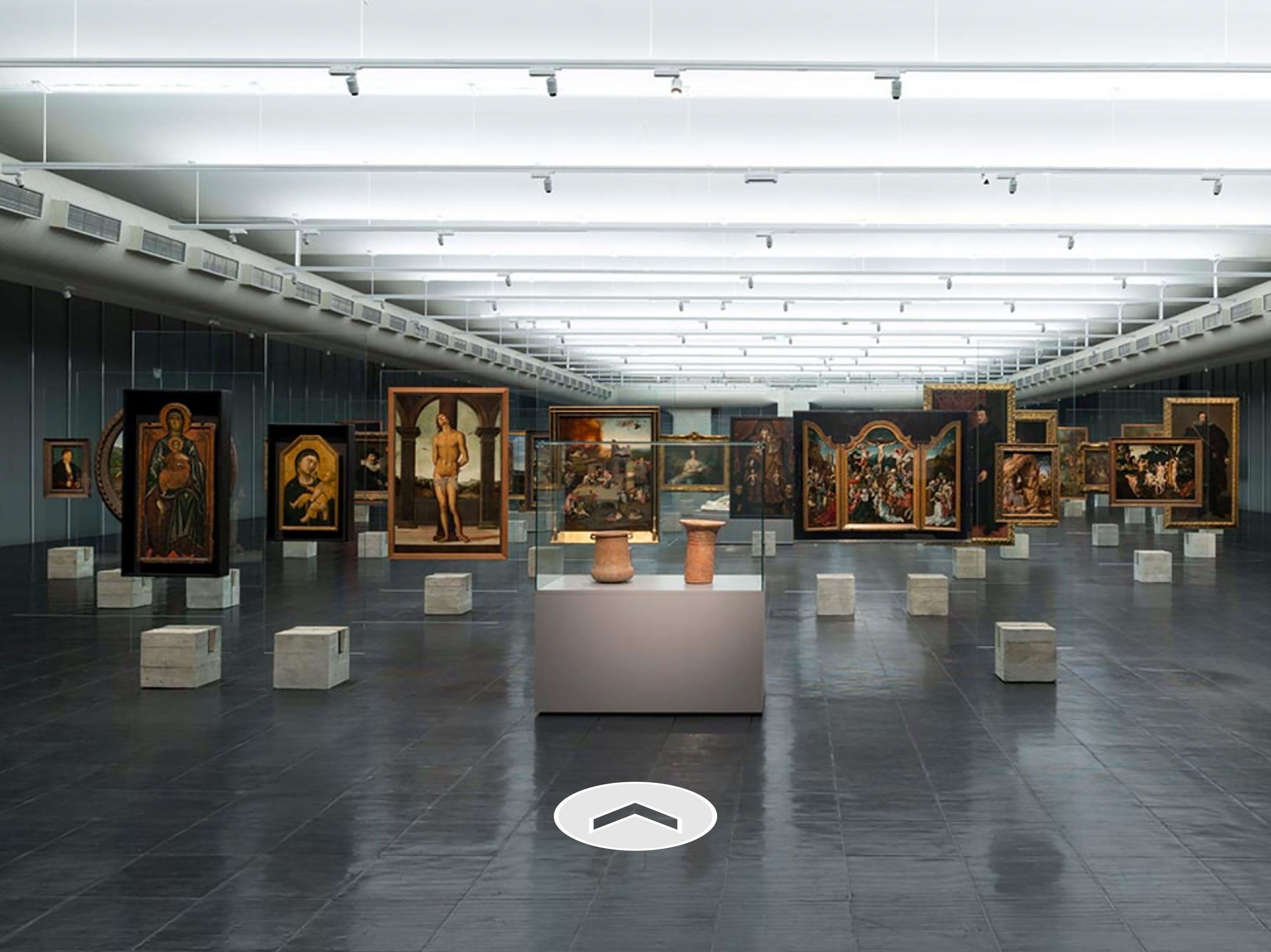 Various paintings lined up in a wide gallery space with a direction arrow at the bottom.