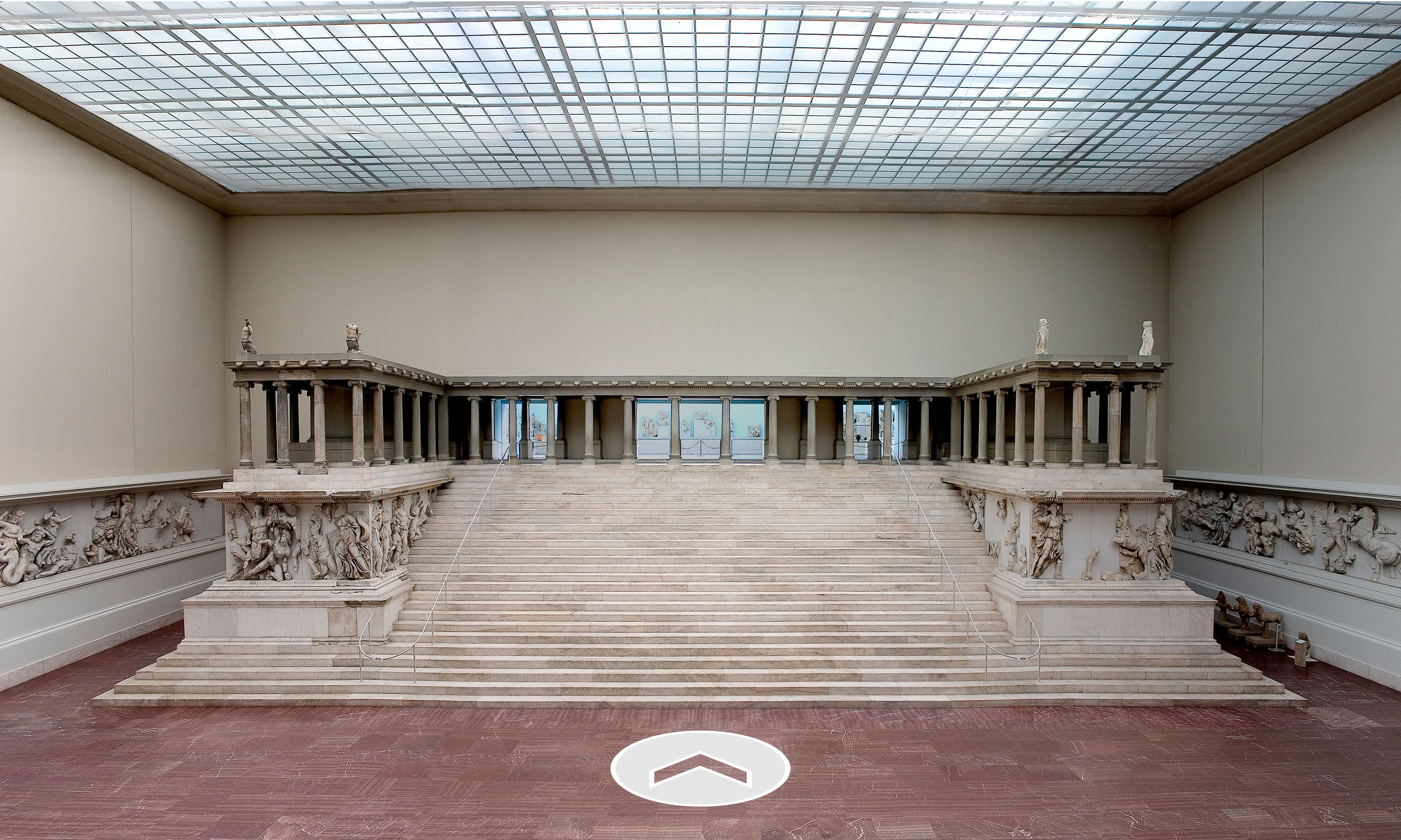 A greek ruin in a large museum space.