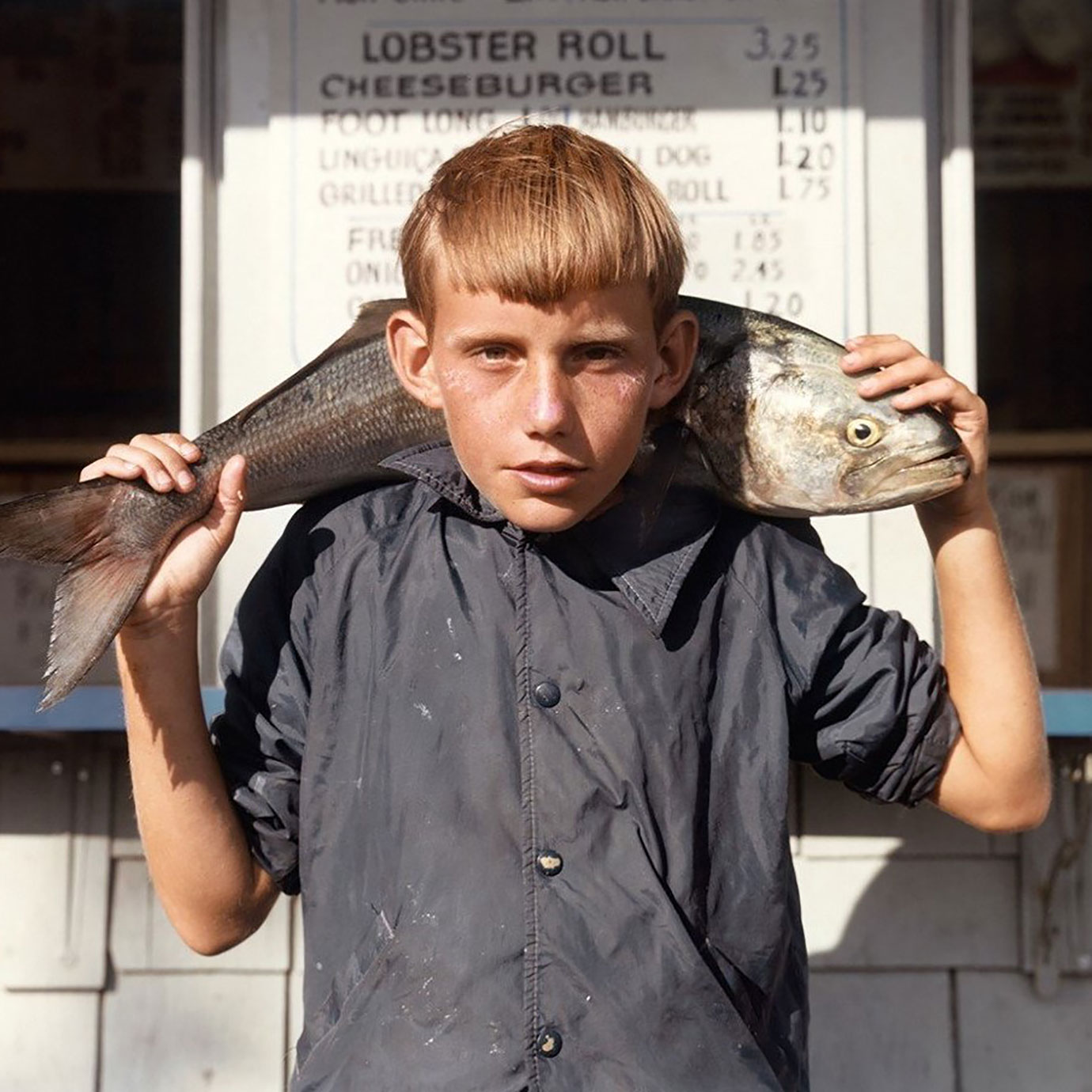 A boy carrying a fish.