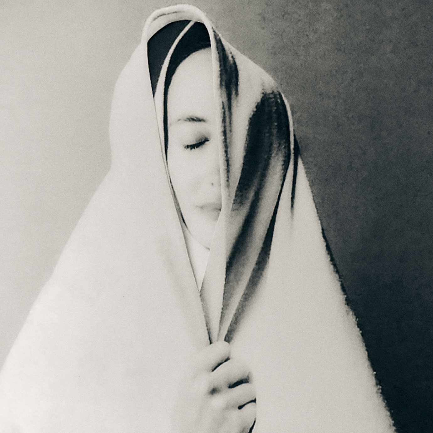 A woman wrapped in a white blanket.