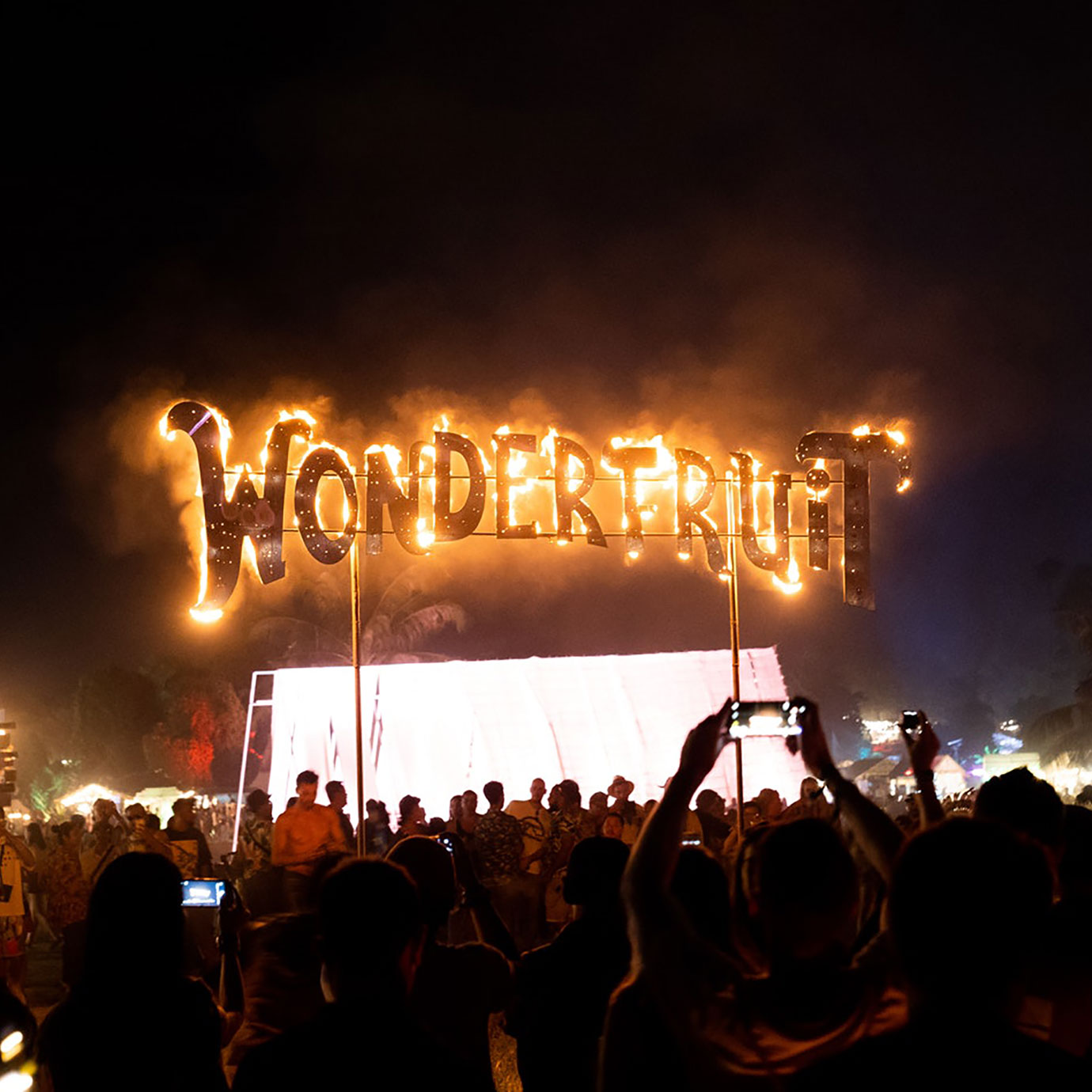 A crowd around a sign with Wonderfruit written in fire on it.