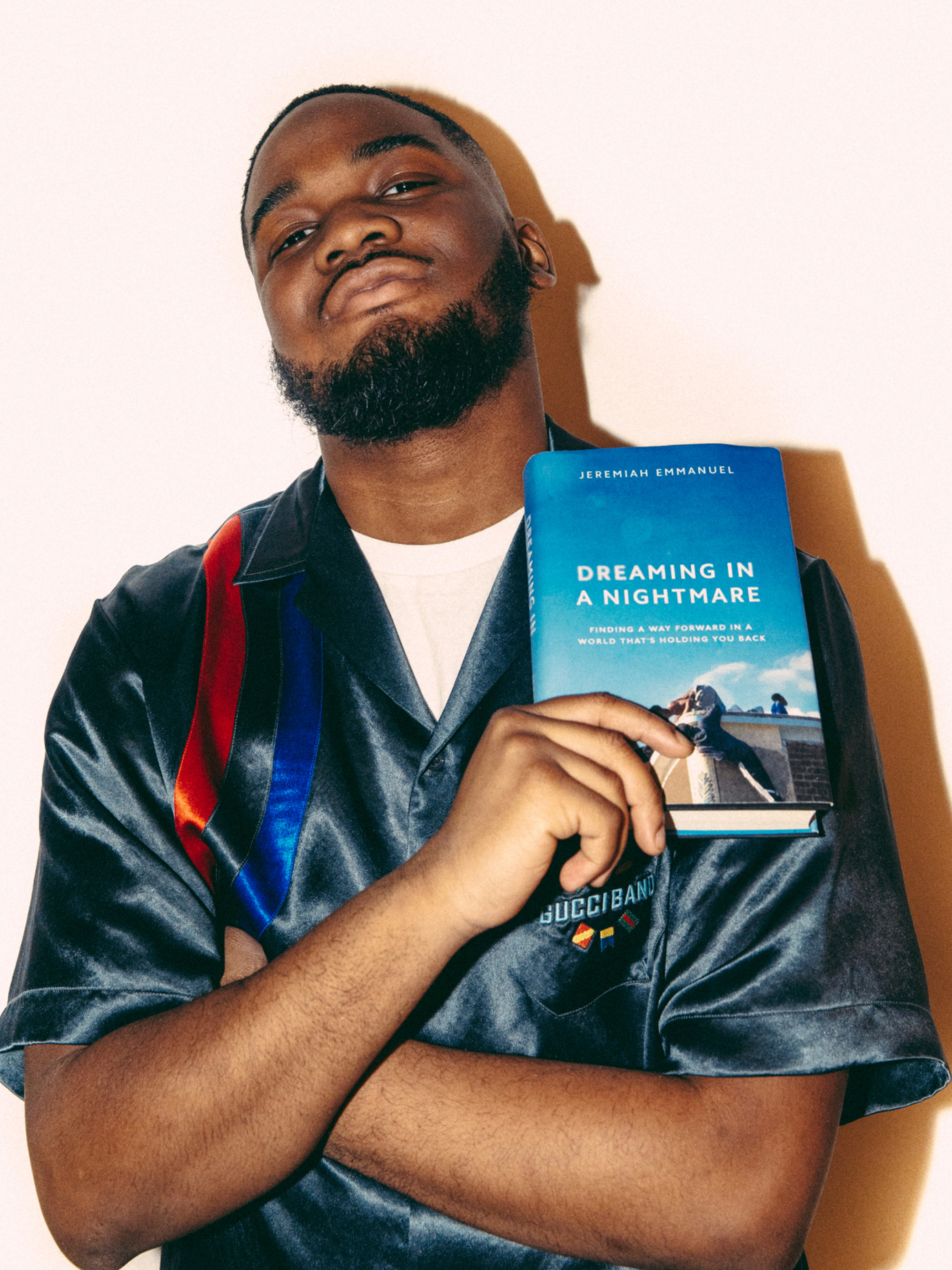 A man holding a book up to his chest.