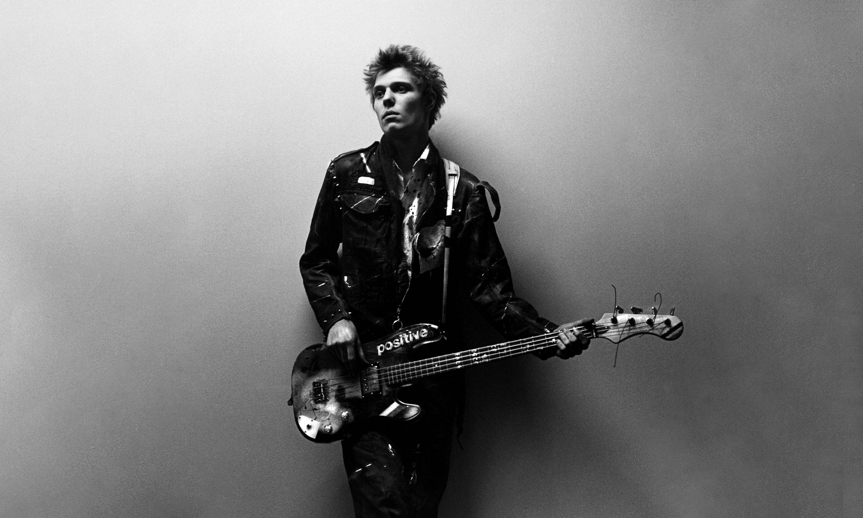 A punk rocker holding a bass guitar.