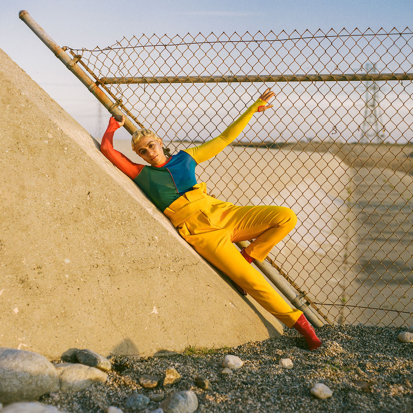 A woman wearing colourful clothing leaning against a concrete wall.