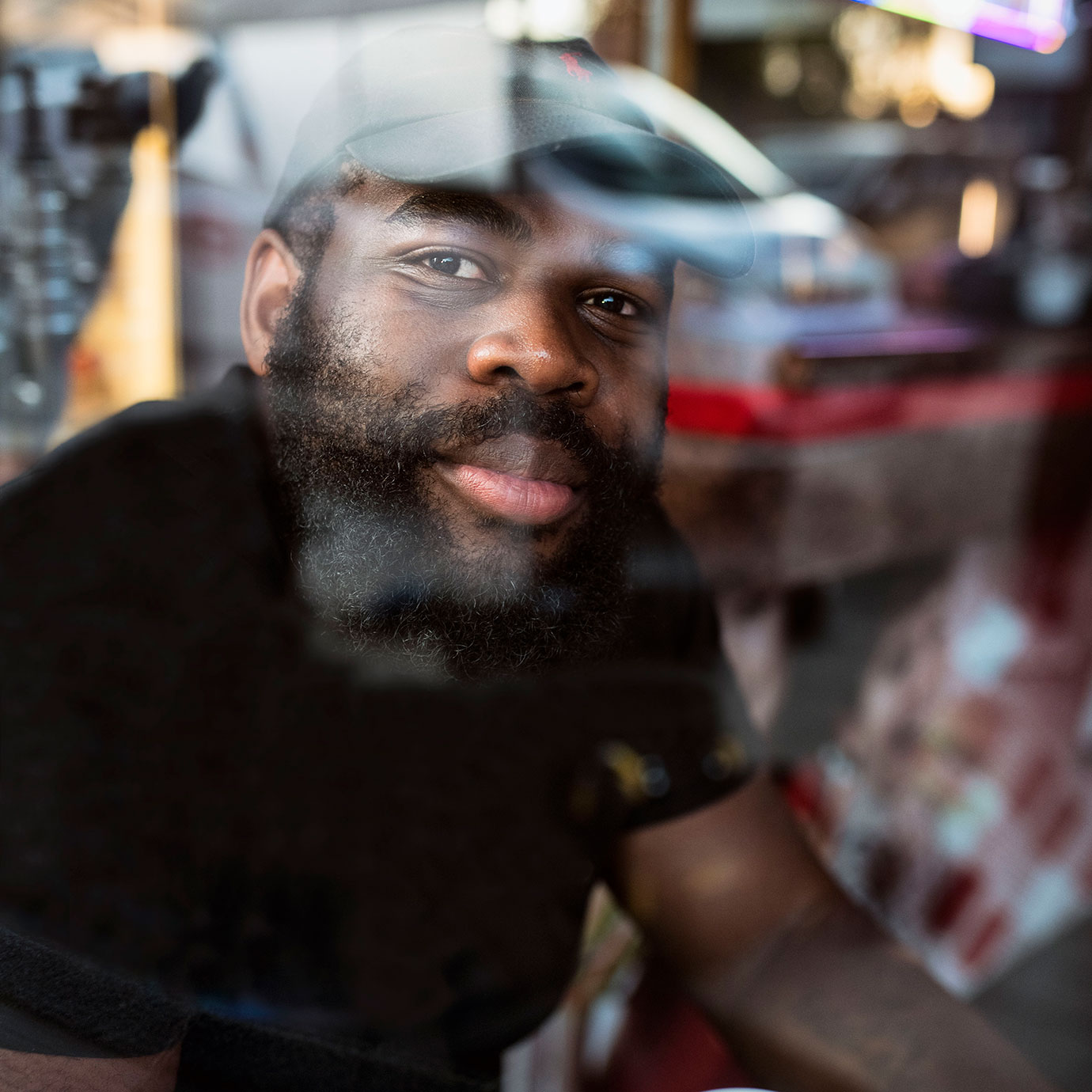 A man sitting on the other side of a cafe window.
