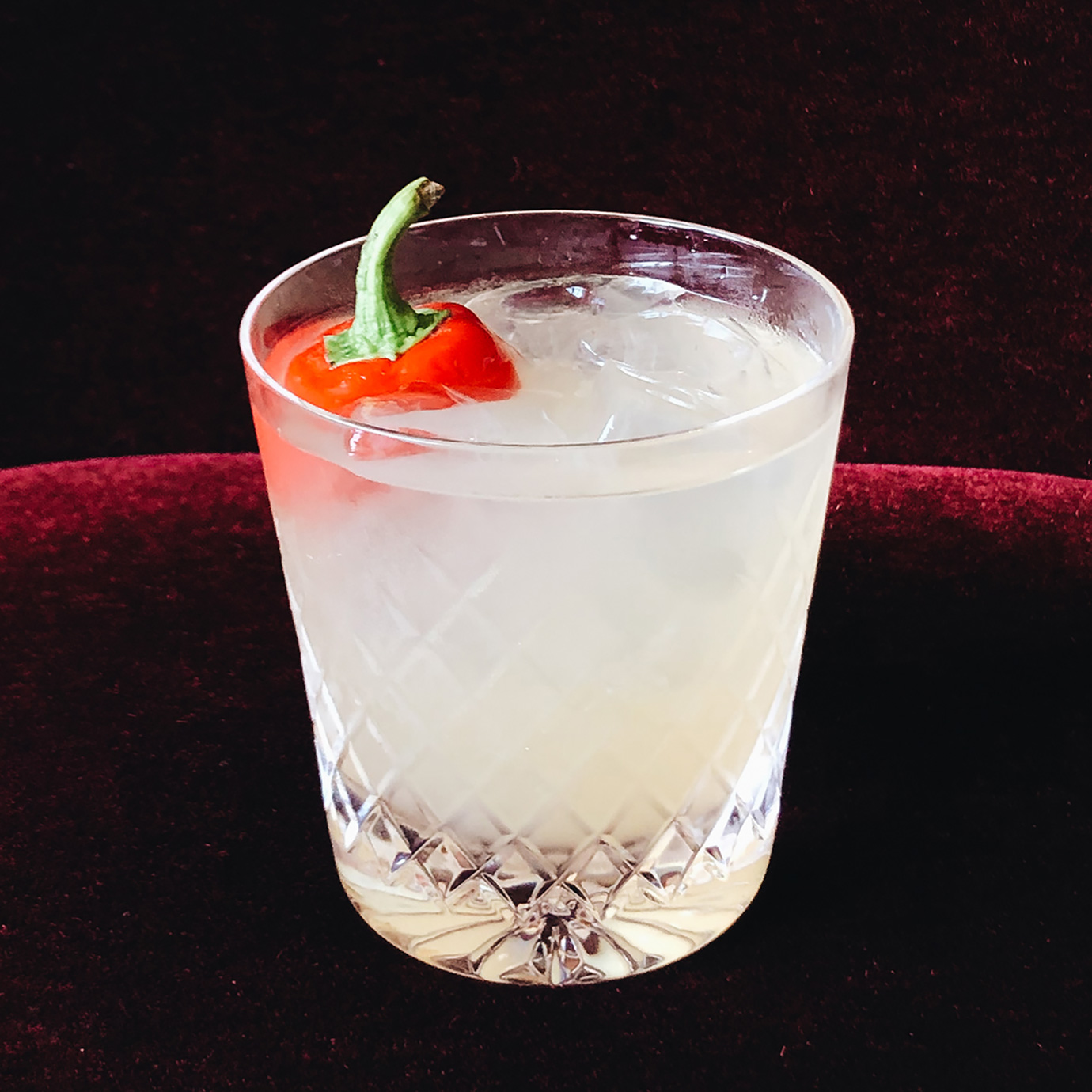 A cocktail with a piece of red chilli in it.
