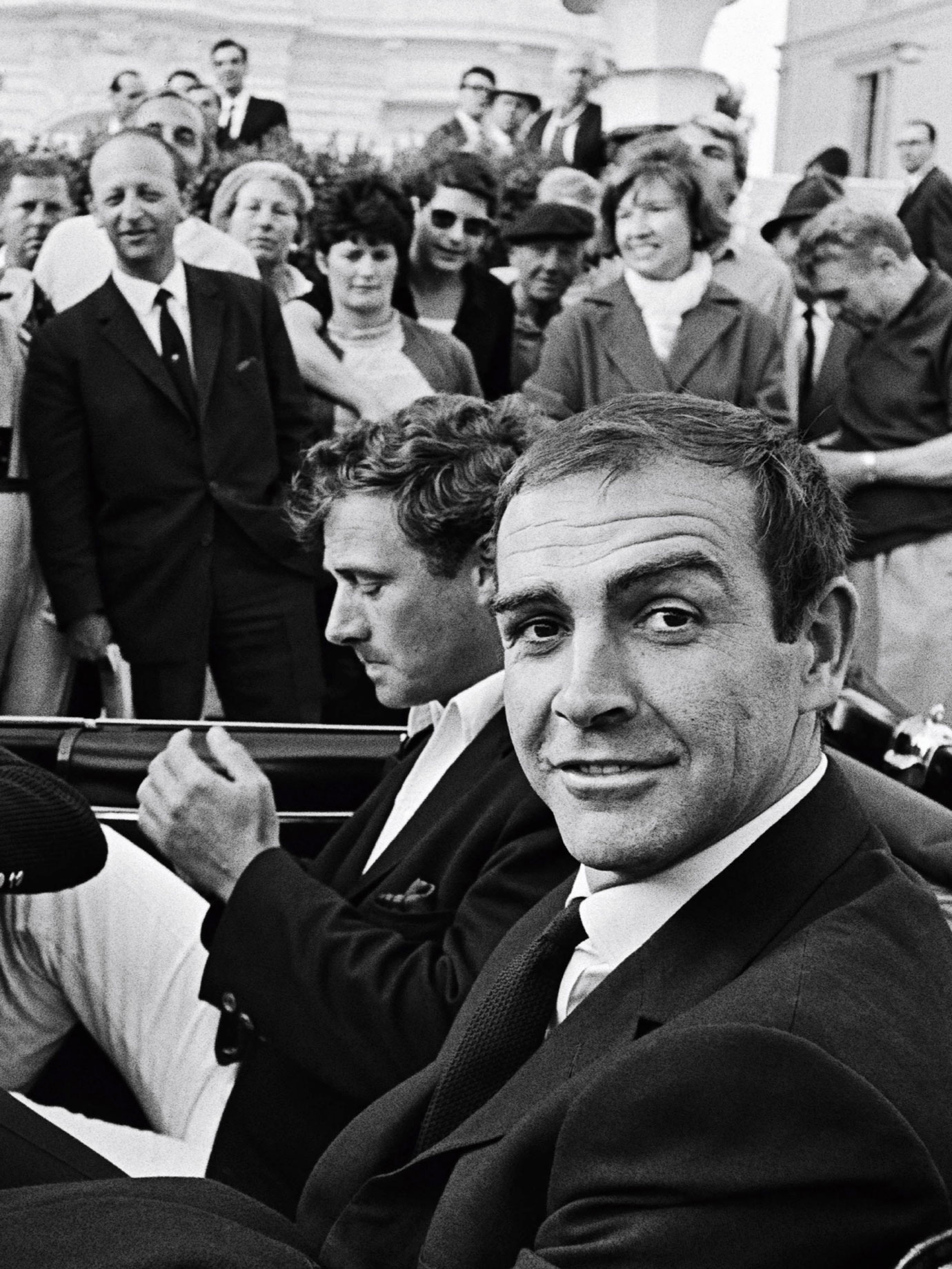 A man smiling at the camera in the back of an open top car as people look on in the 1960s.