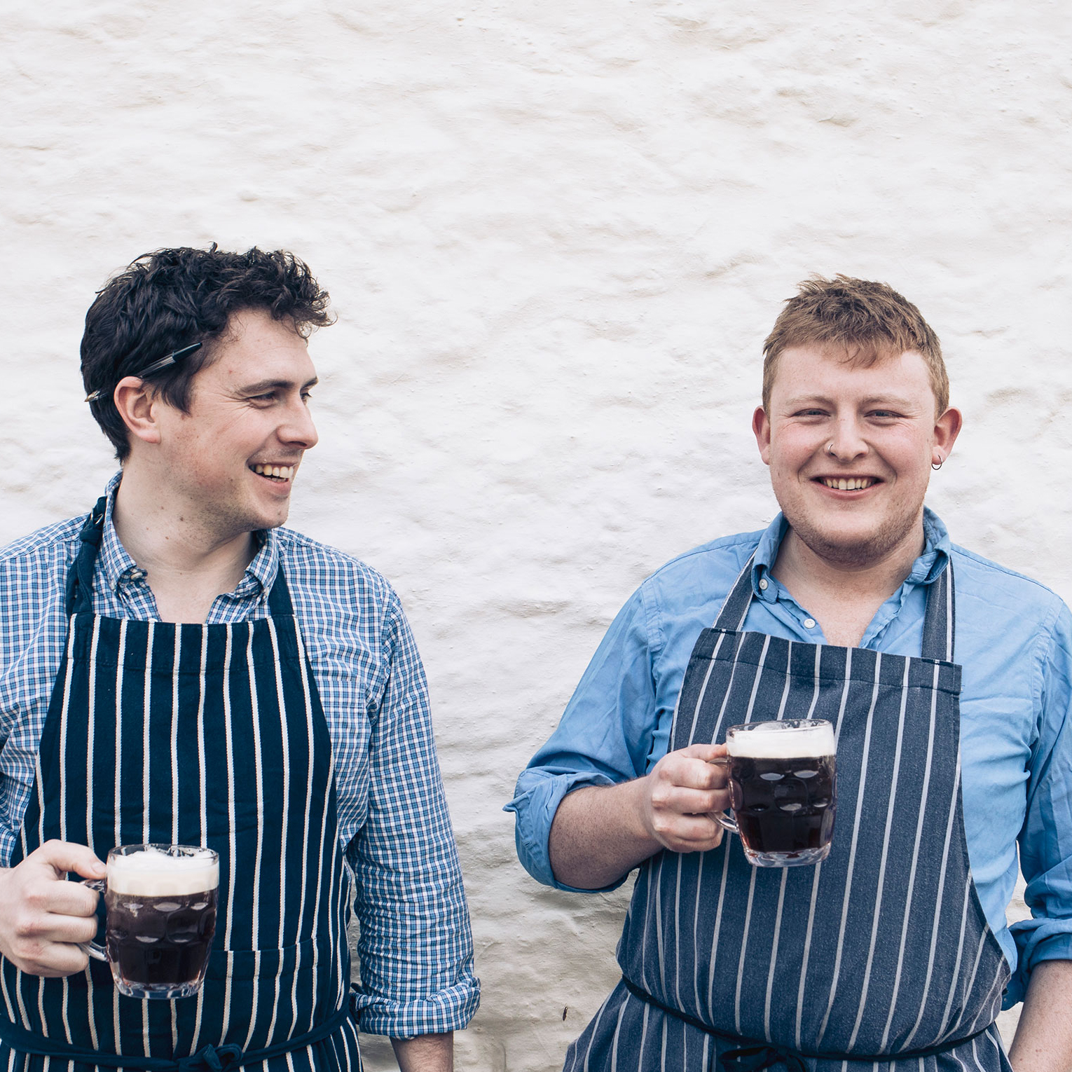 two men holding beers in aprons
