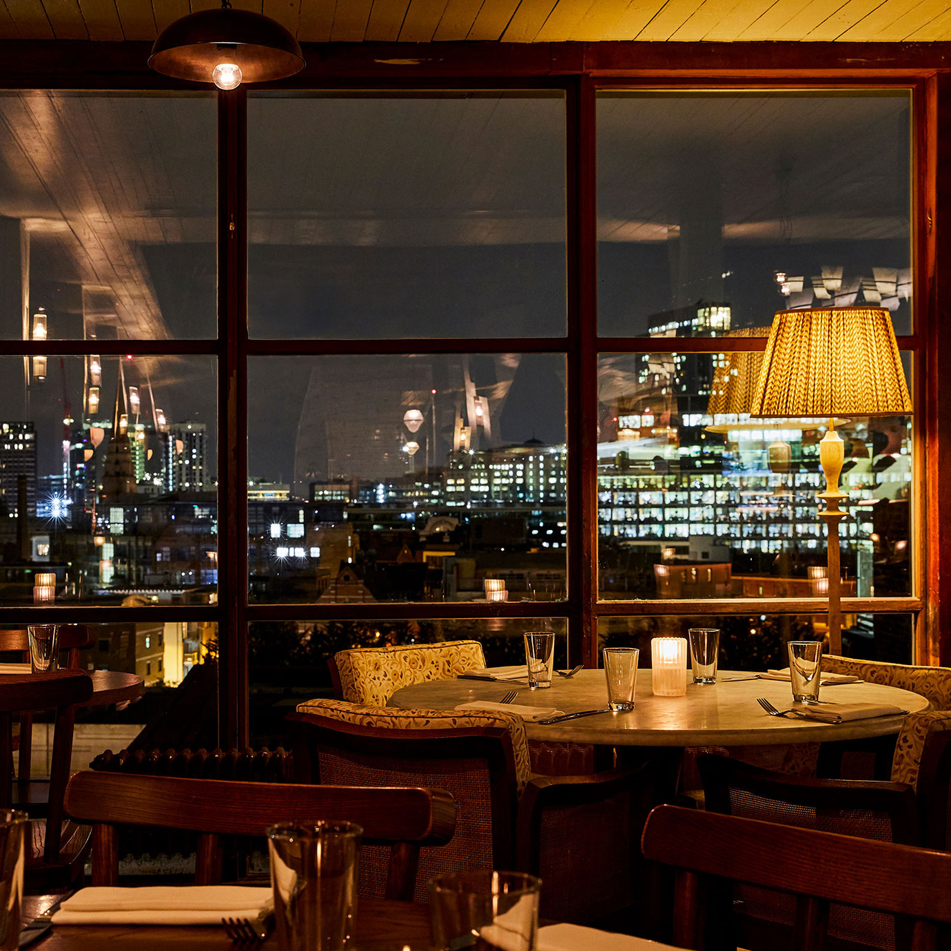A restaurant at night with panoramic views of a city.