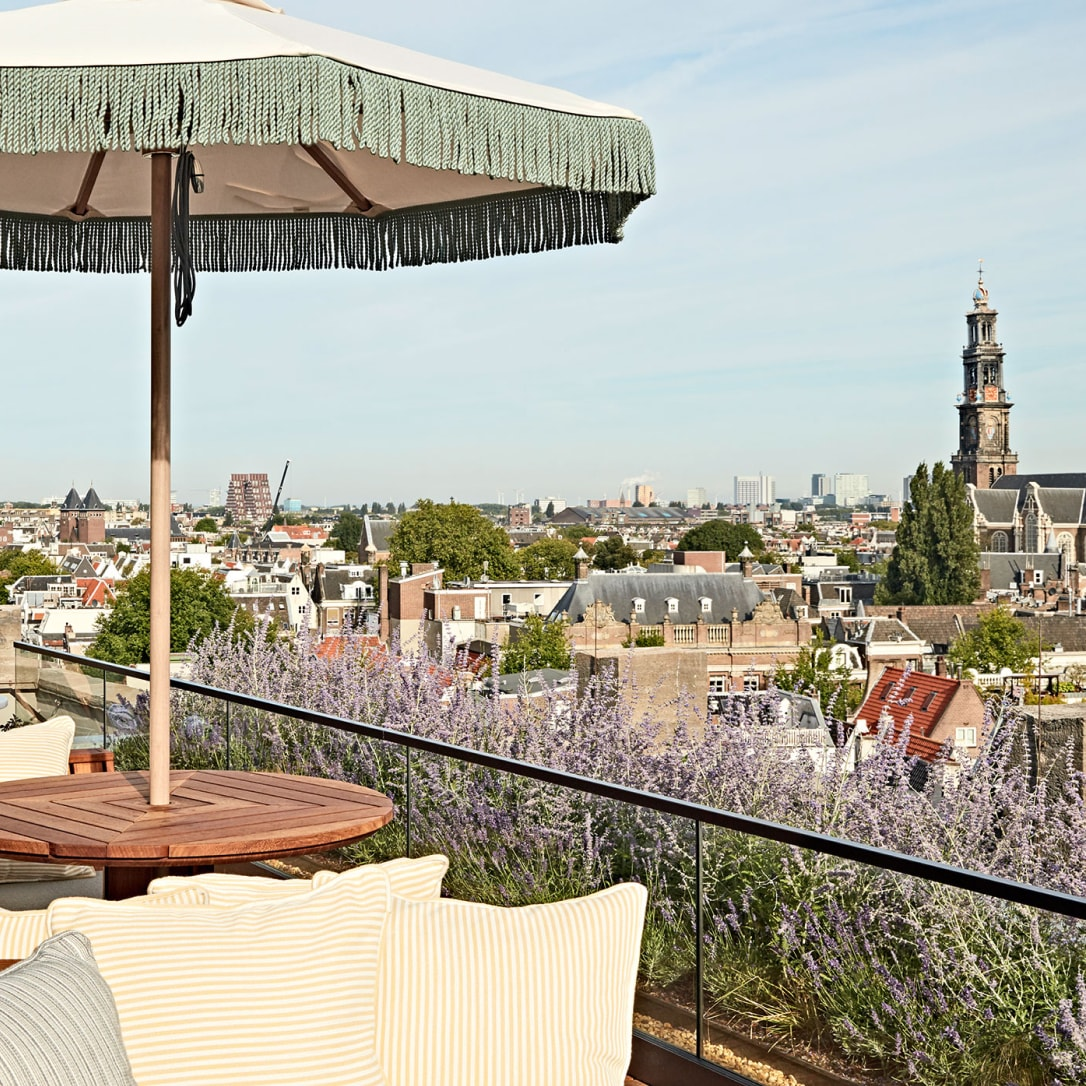 A rooftop table and seating overlooking an Amsterdam street.