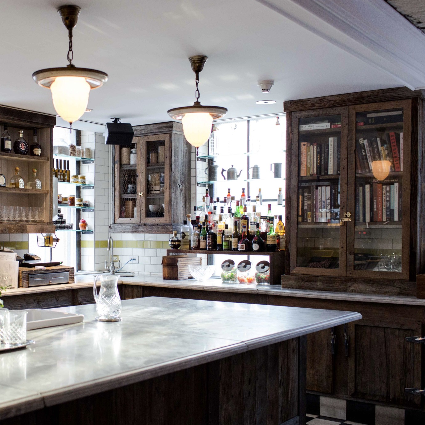 The interior of a pantry type bar with a large serving surface and cupboards on the walls.