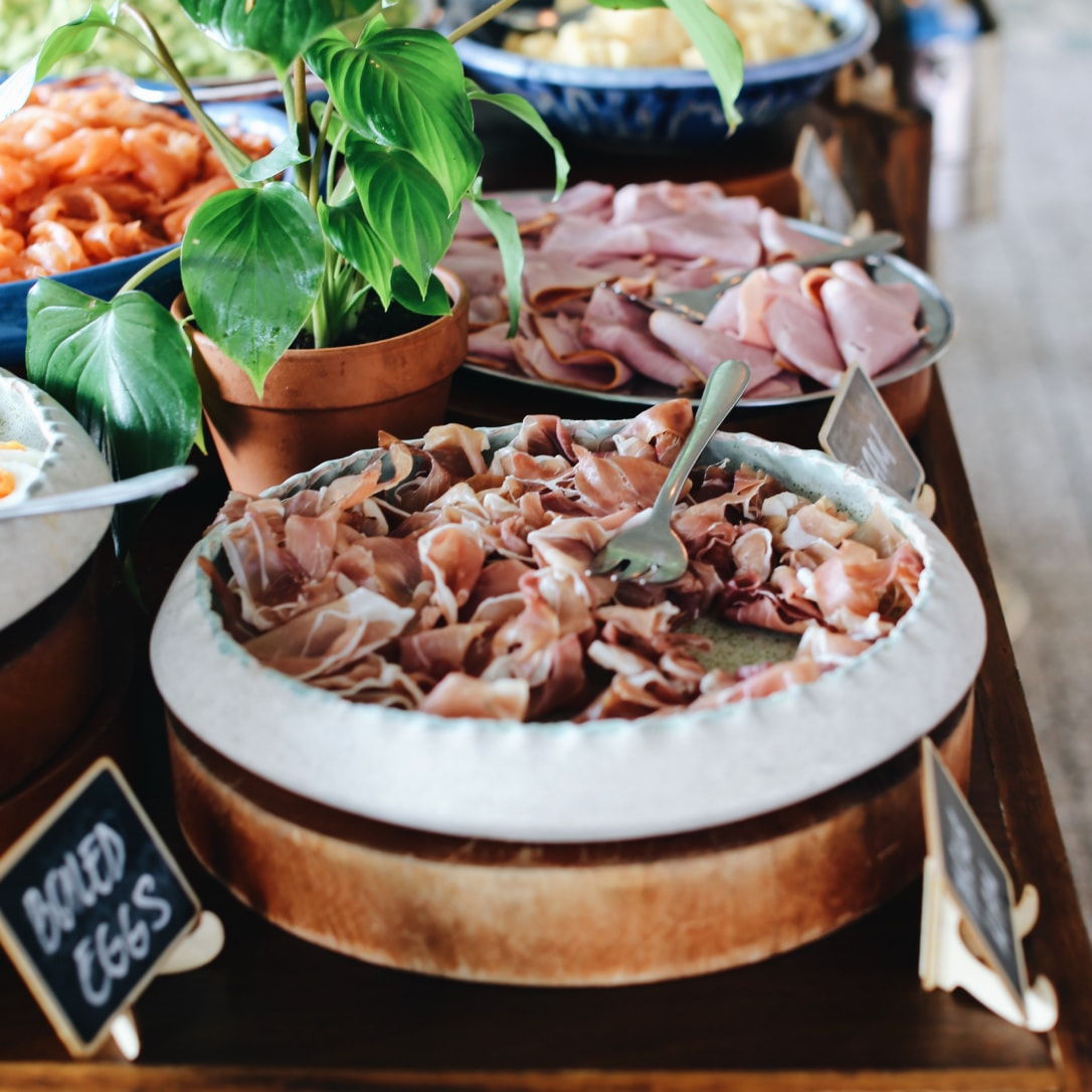 A buffet with cold meats on a plate.