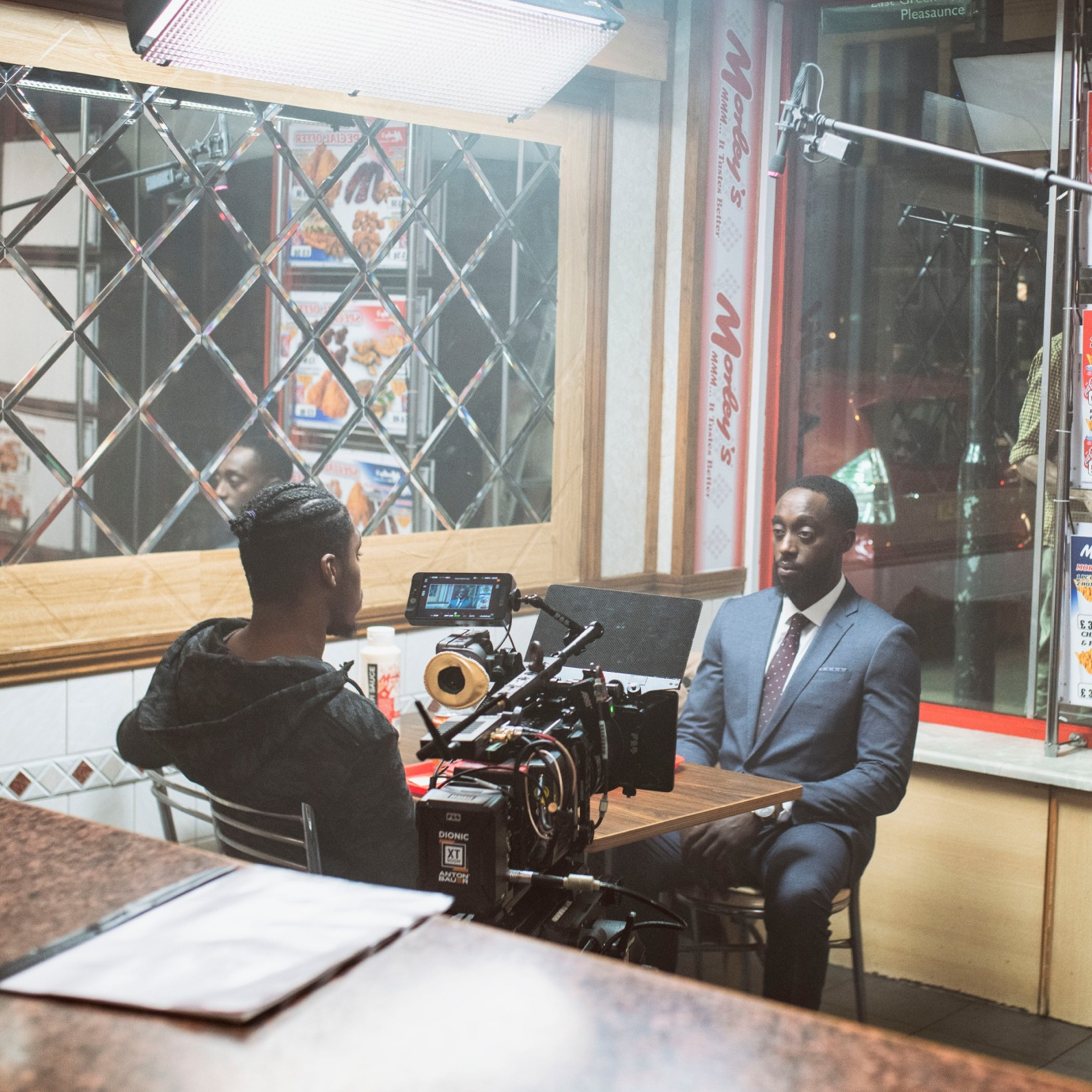 Two men sat at a cafe table in a film set with film cameras and lights.