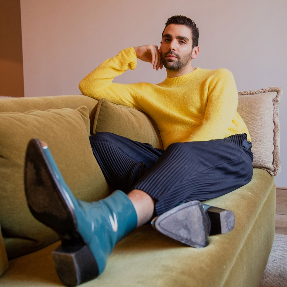 A man lyiing with his boots up on the sofa.