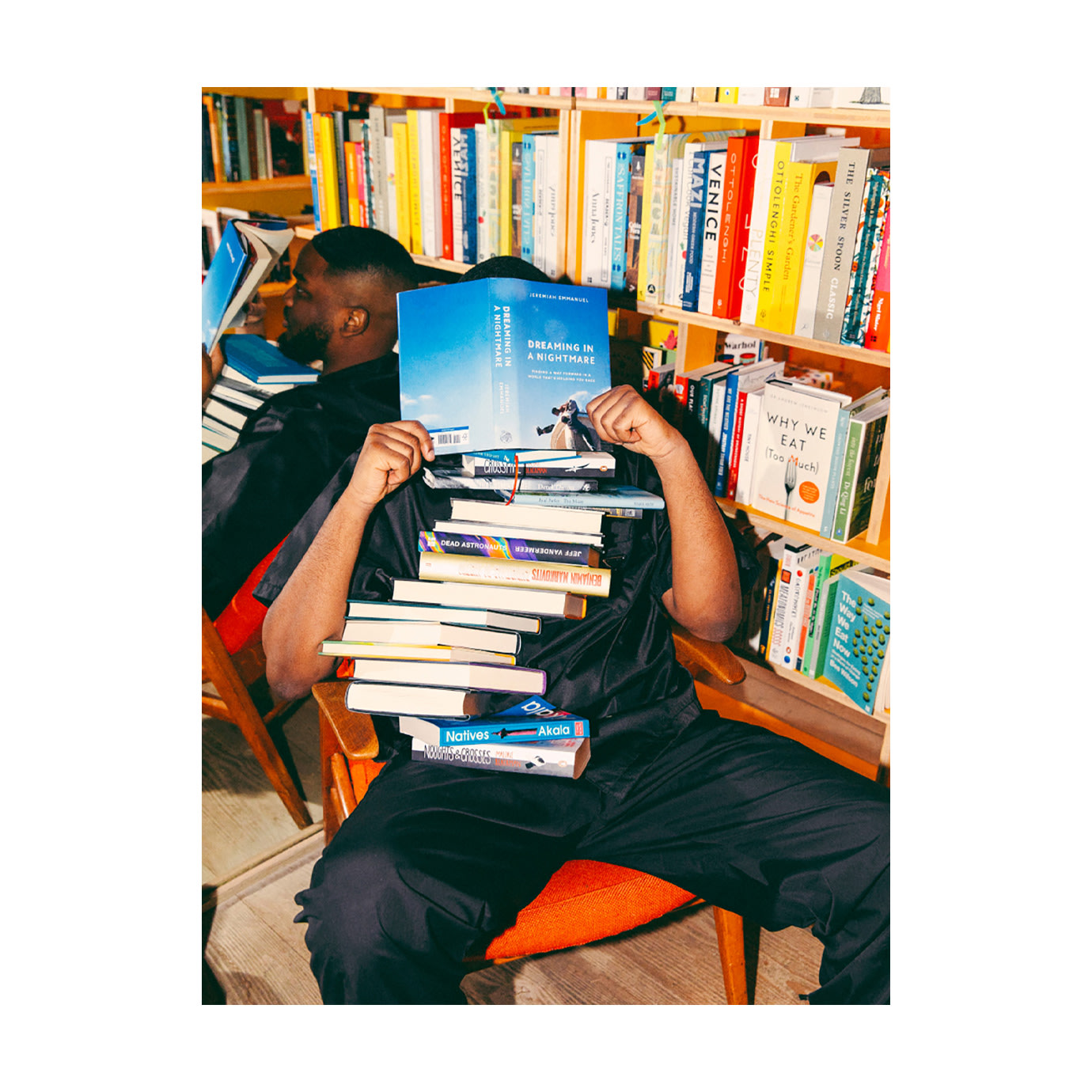 A man covered in a pile of books next to a yellow bookcase.