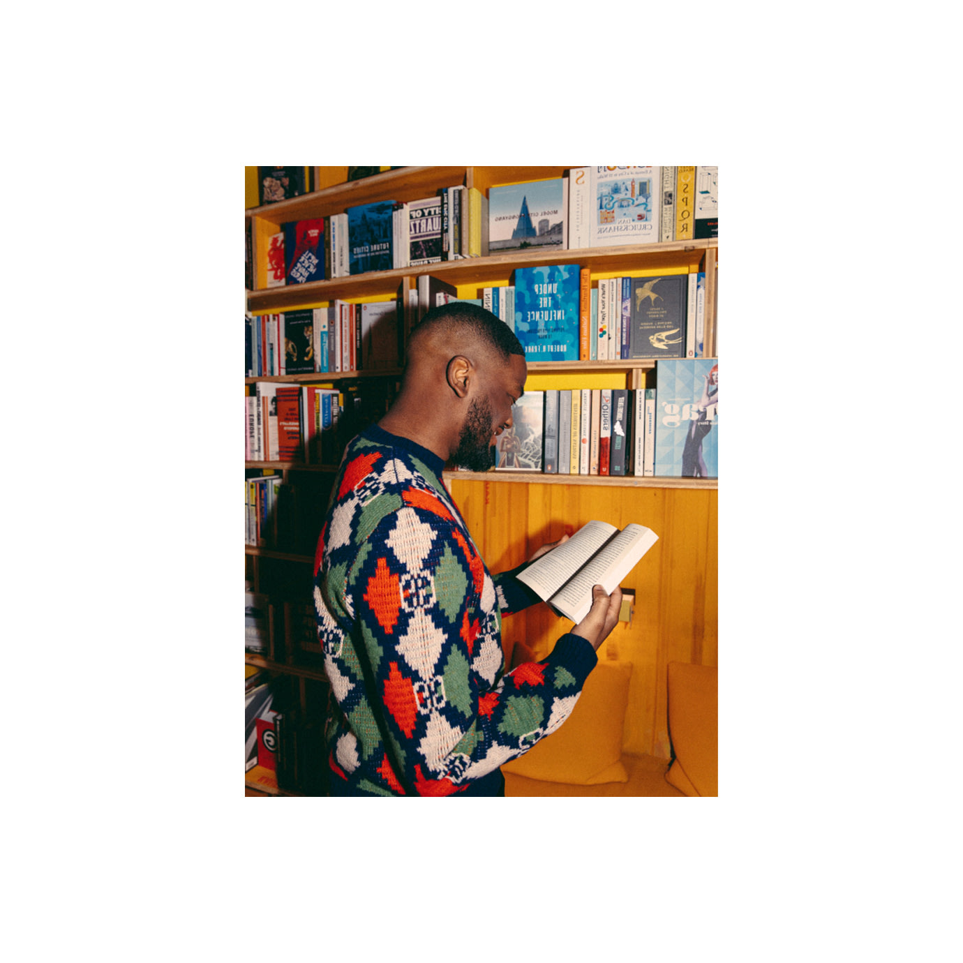 A man reading a book next to a yellow bookcase.