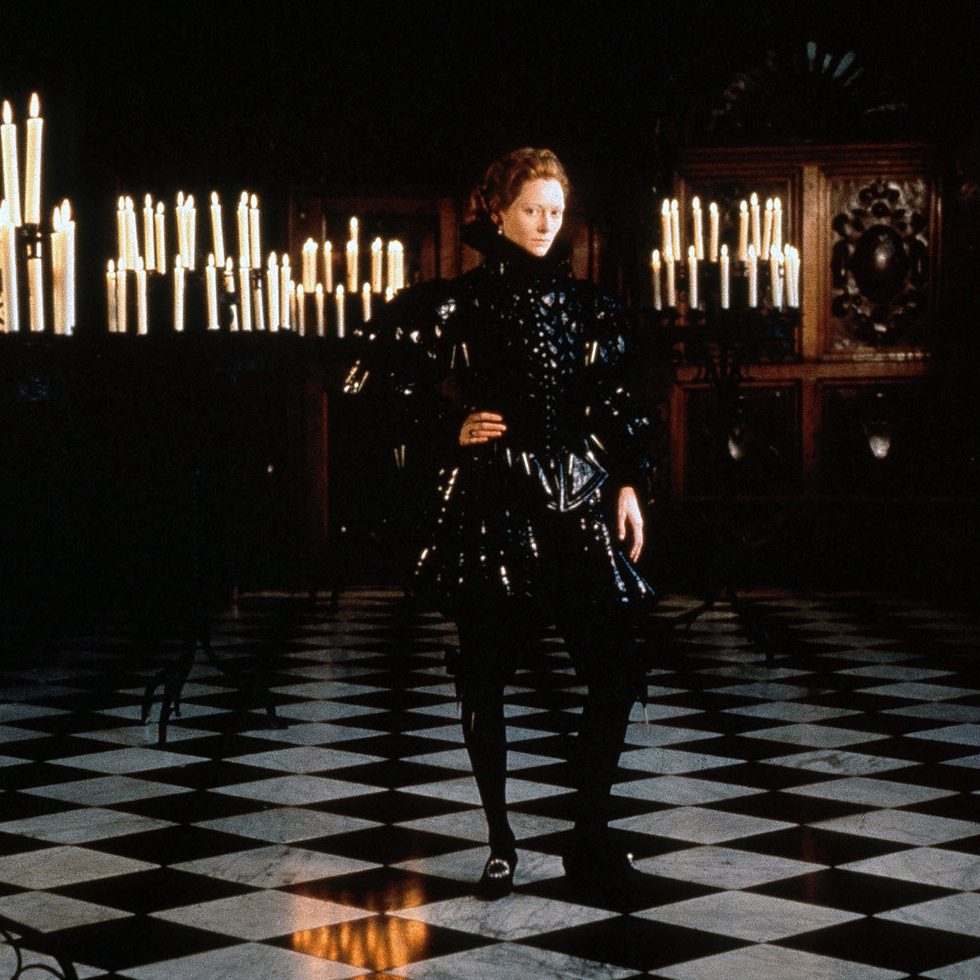 A woman wearing men's Elizabethan dress in a dark room with candles.