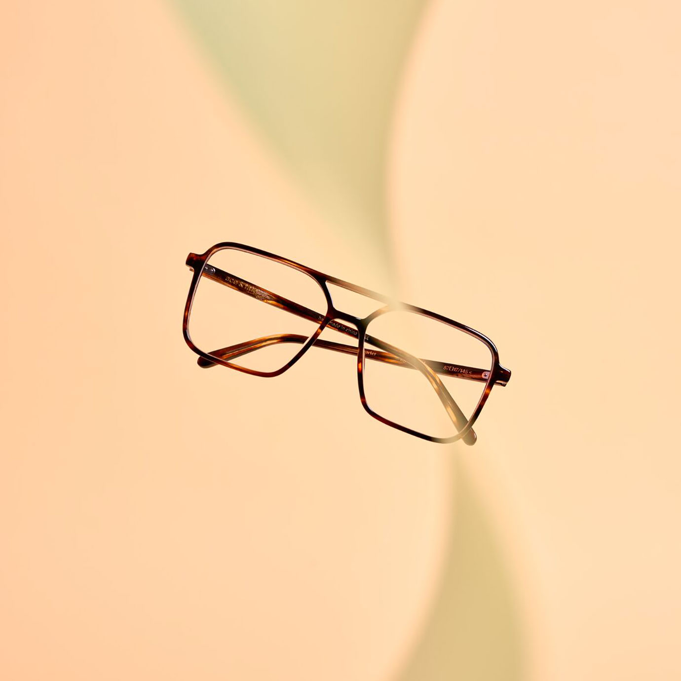 Glasses floating on a peach background.
