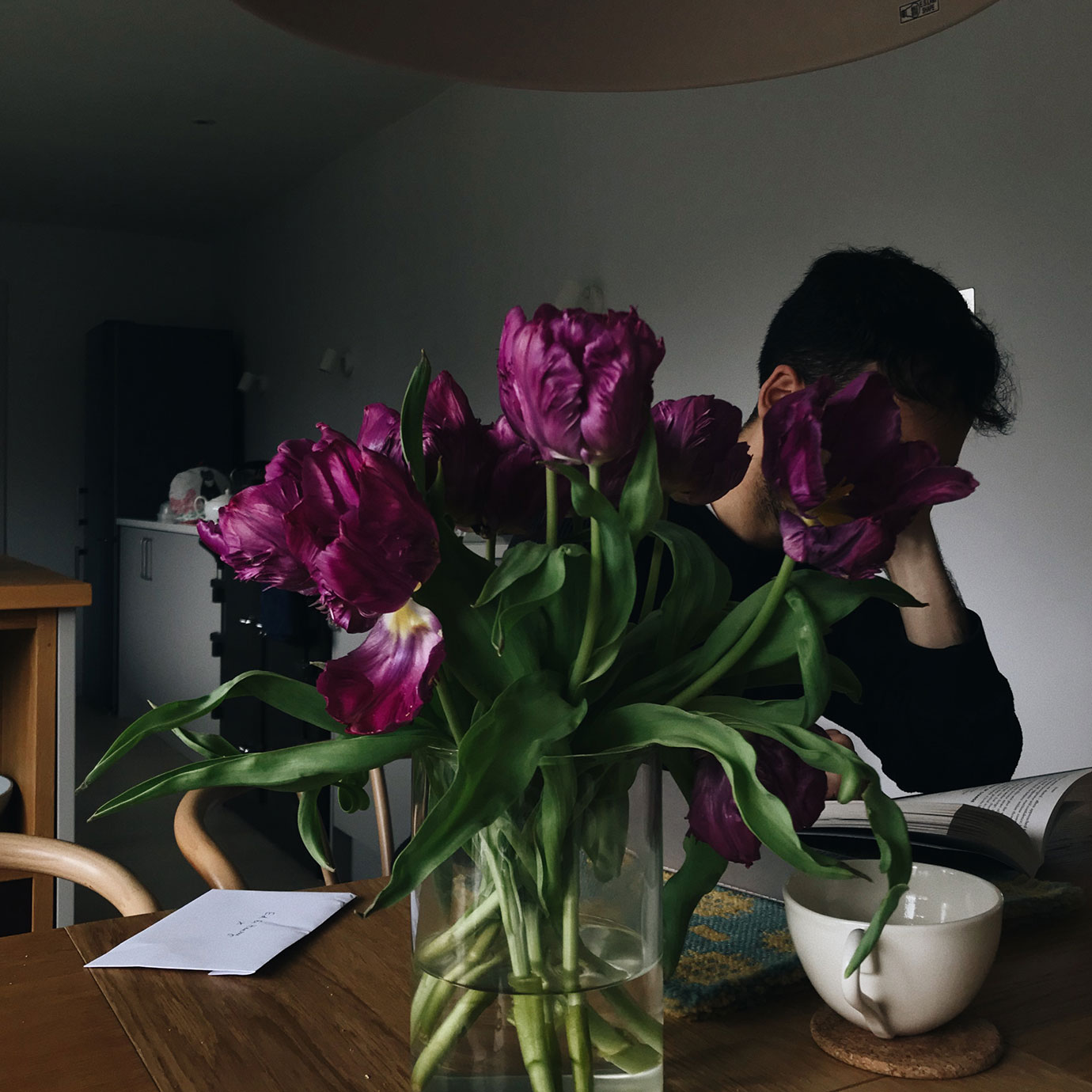 A vase of purple flowers with a person behind them.