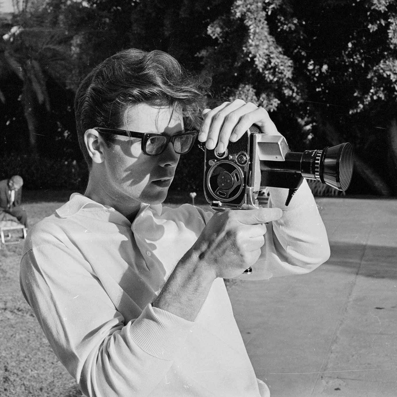 A vintage black and white photograph of a man using an old film recording camera in a garden.
