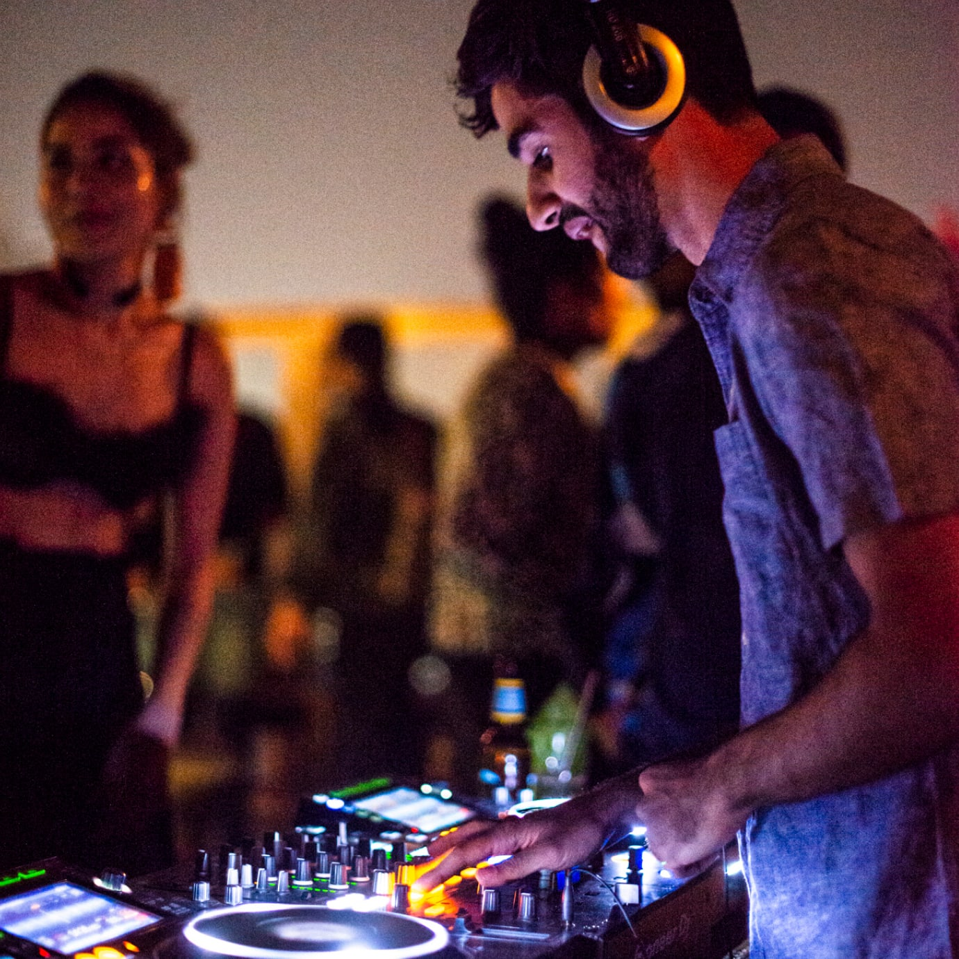 A man DJs on a rooftop with people dancing around him.
