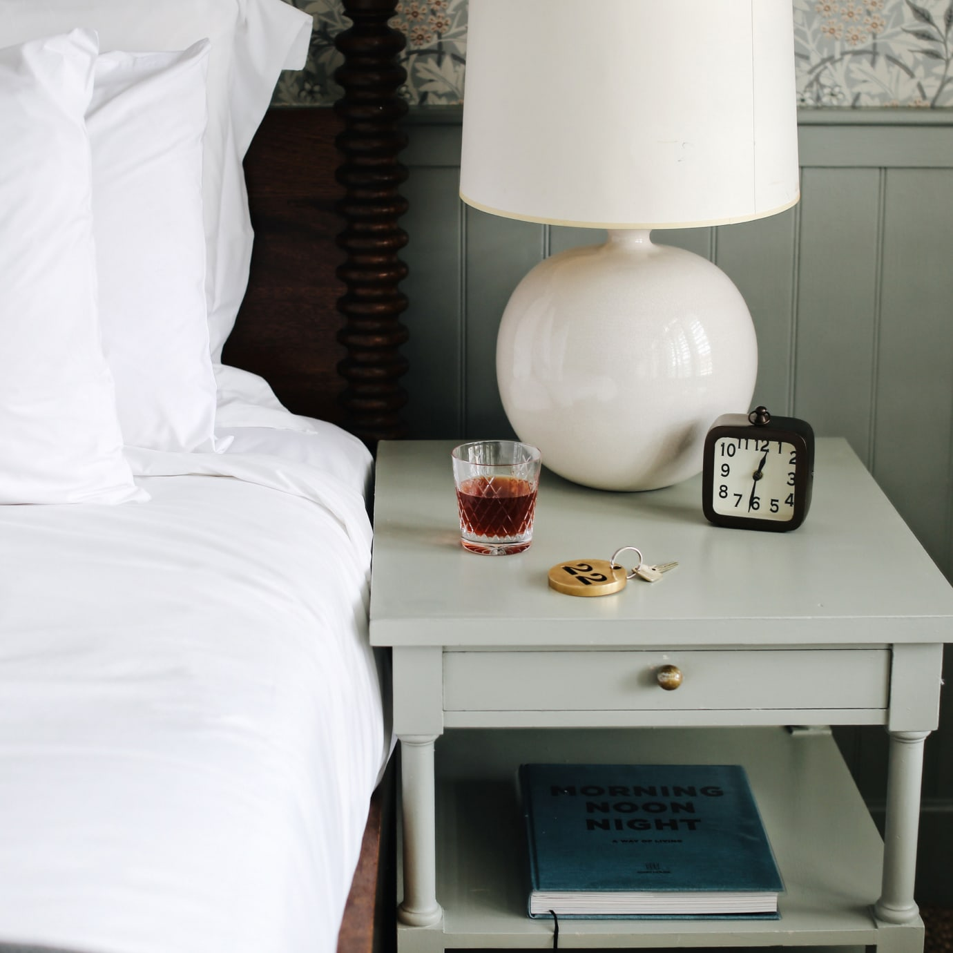 The side of a bed and a bedside table with a drink in a cut crystal glass on it.