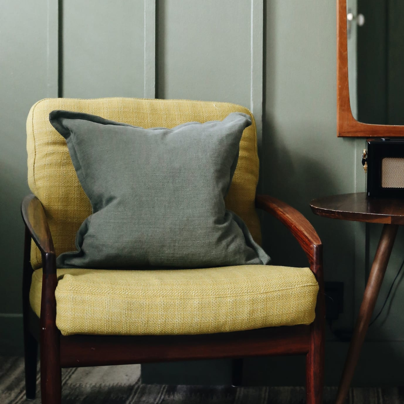A yellow armchair with a cushion on it.