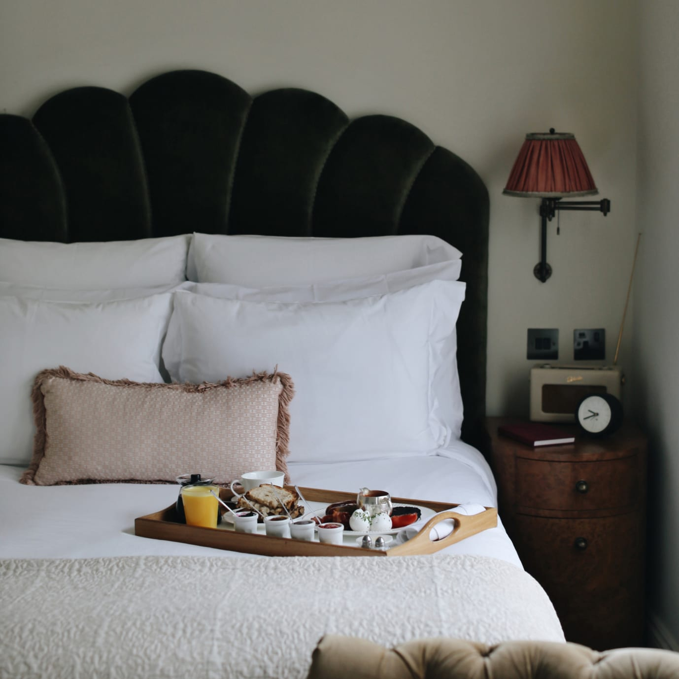 A bed with room service on it on a tray.