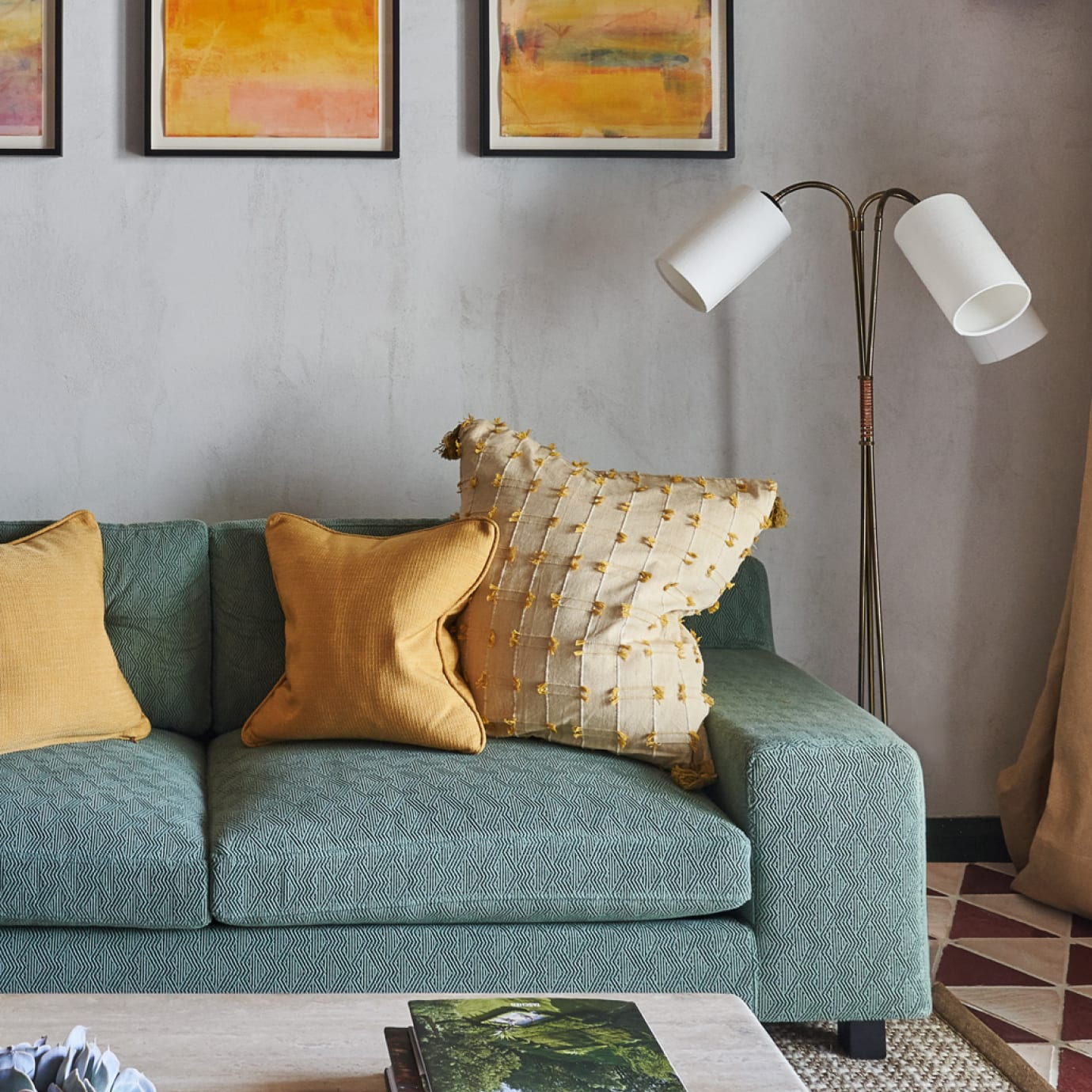 A blue sofa with cushions next to a floor lamp.