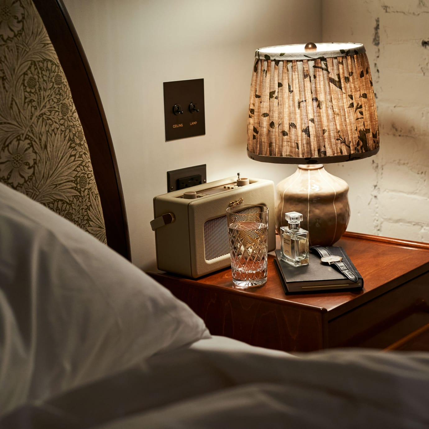 A bed and bedside table at night.