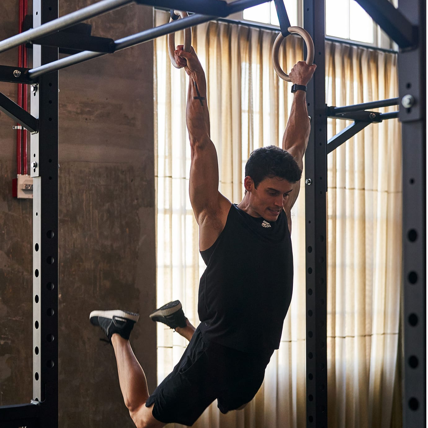 A man swings on fitness rings in a gym.