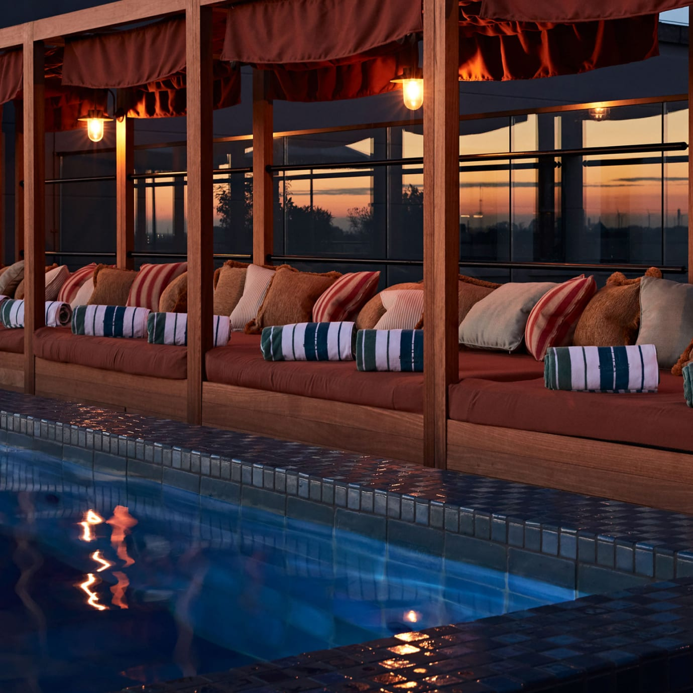The corner of an outdoor pool and a row of daybeds at sunset.