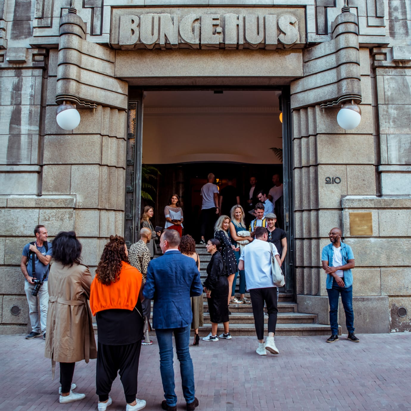 A group of people standing outside the entrance to a concrete building with Bungehuis written on it.