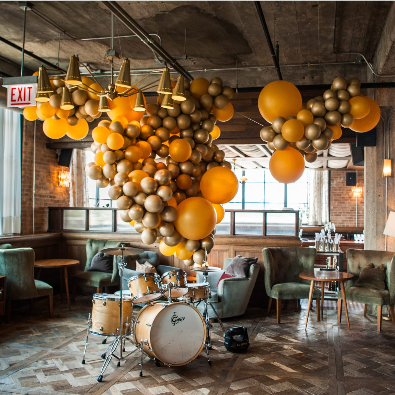 A balloon installation in a room above a drum kit.