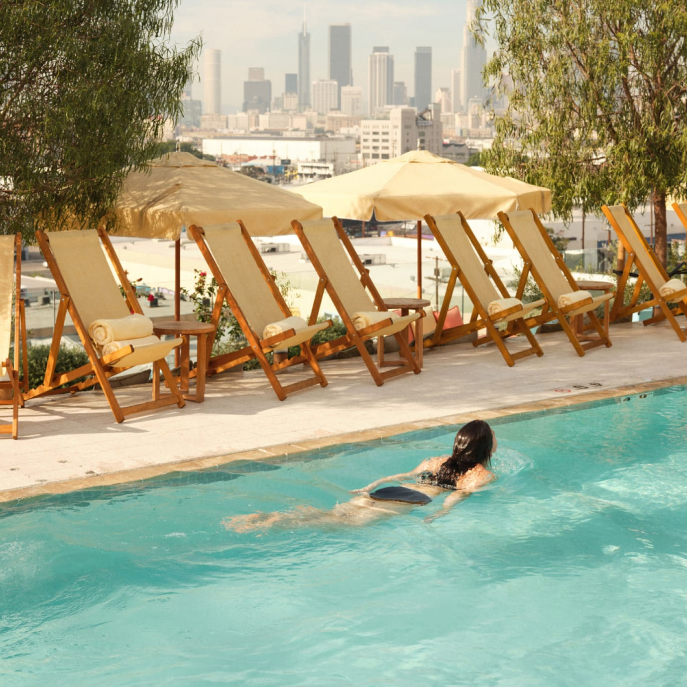 A woman swimming in a rooftop pool.