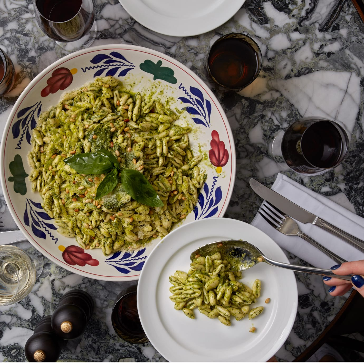 A person dishing out a plate of pasta from a sharing plate.