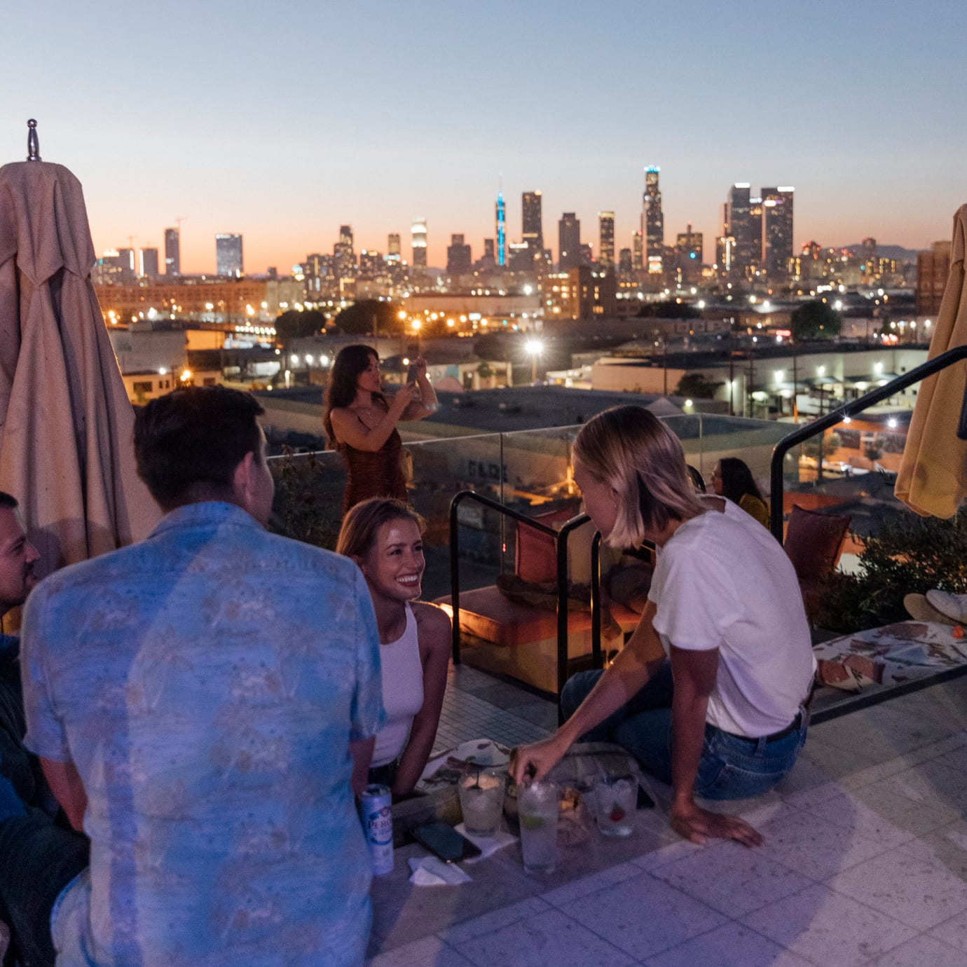 A group of men and women drinking and chatting on a rooftop.